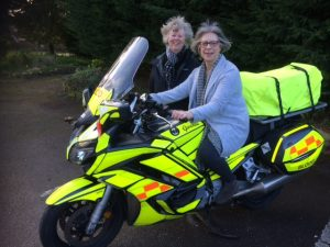 Sally Rees (WCVA) and Val Conelly (AVOW) sit on a Blood Bike Wales motorbike