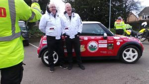 Chris and John from Blood Bike Wales stand near a Mini Cooper on their trip