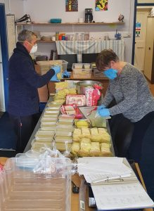 Volunteers at Hive community cafe prepare meals for delivery