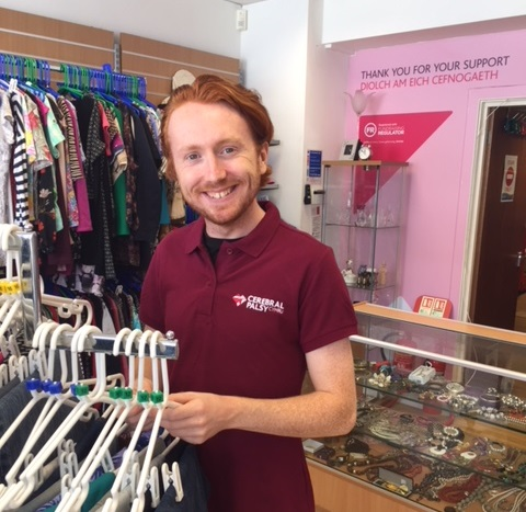 Volunteer wearing Cerbral Palsy Cymru t-shirt stands in charity shop smiling widely in front of a clothes rail, there are more clothers and other wares in the background