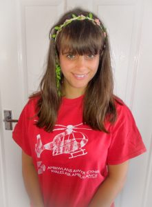 Young Wales Air Ambulance volunteer, Danni, in her red Ambiwlans Awyr Cymru Wales Air Ambulance t-shirt