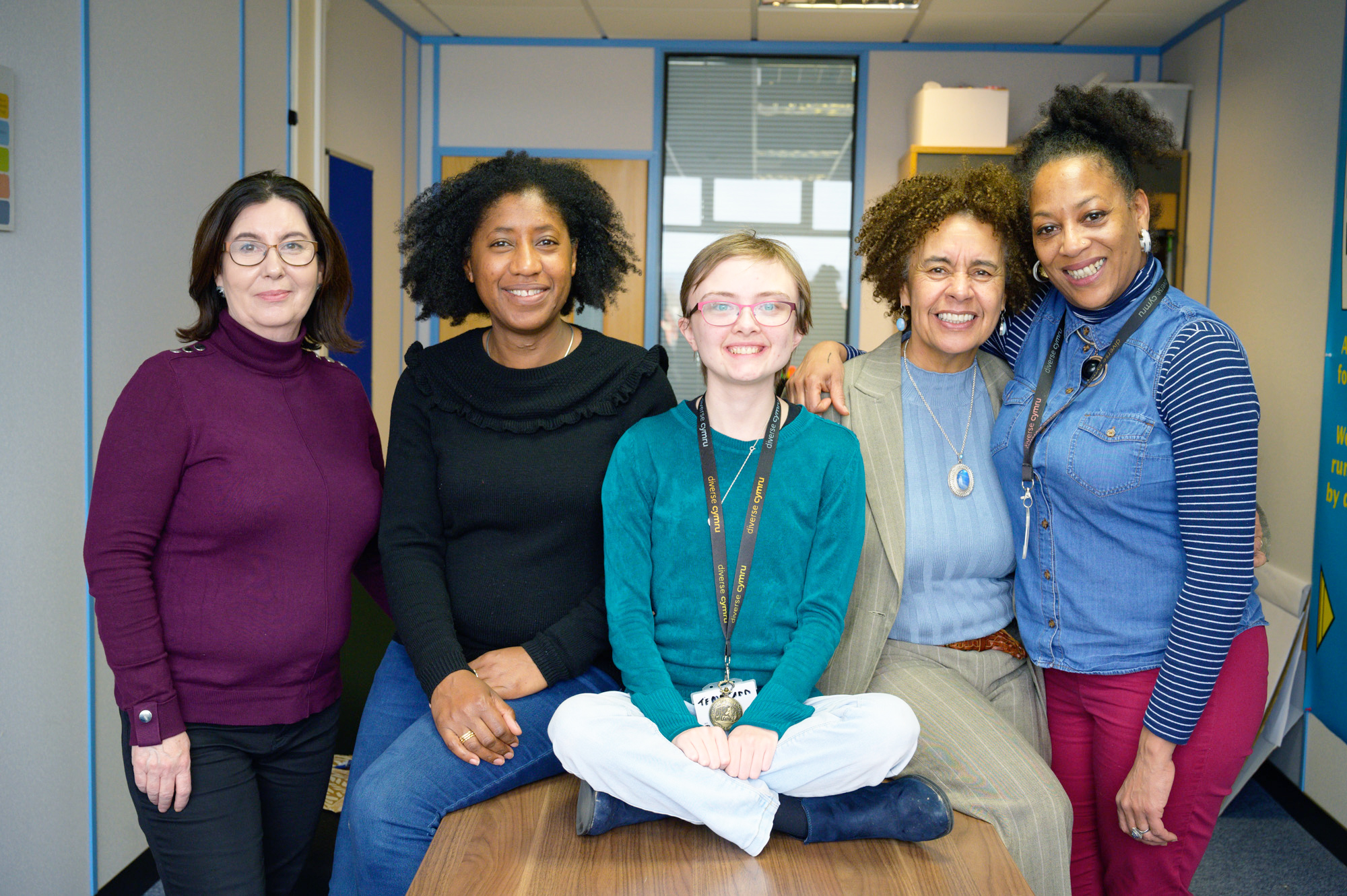 A group of smiling women sit on a desk in an office