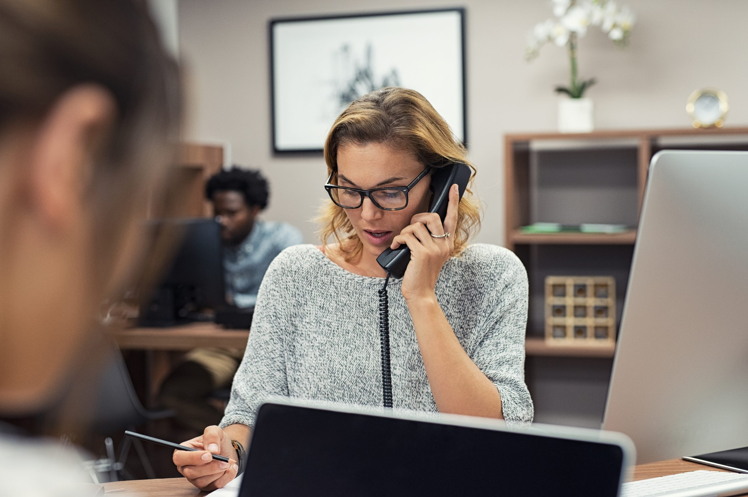 Woman in office talks on the phone while taking notes