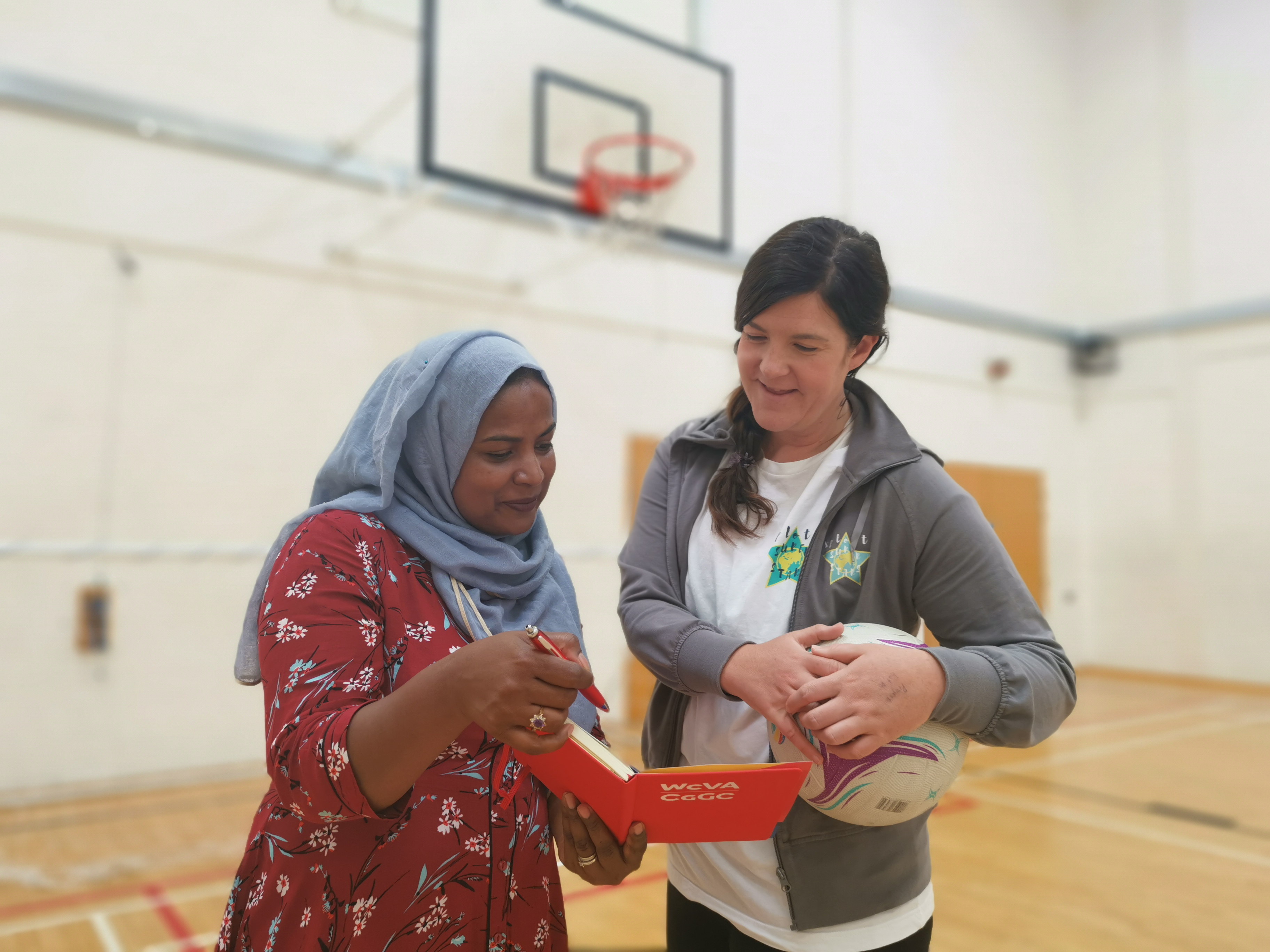 Two women in a leisure centre hall share notes as they look at a workbook
