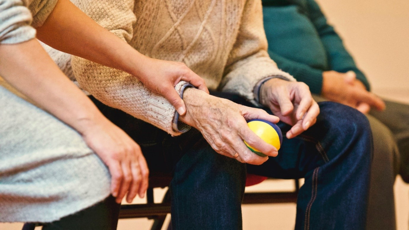 A social/care worker holds the hand of an older person as they hold onto a juggling ball