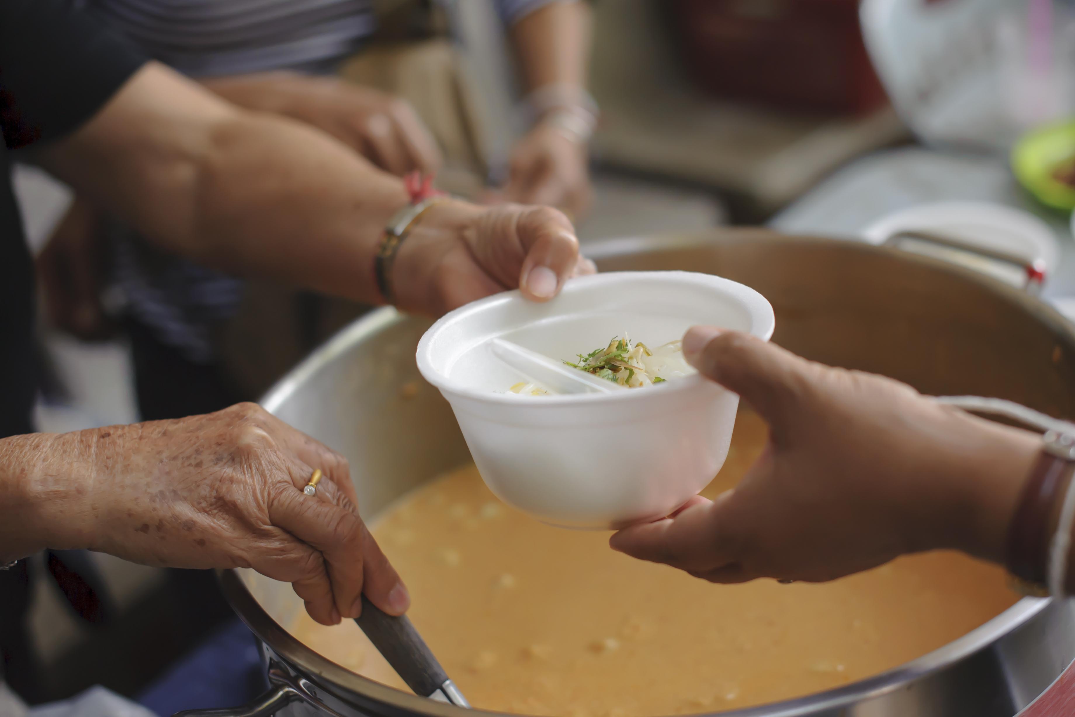 Volunteer handing soup to someone