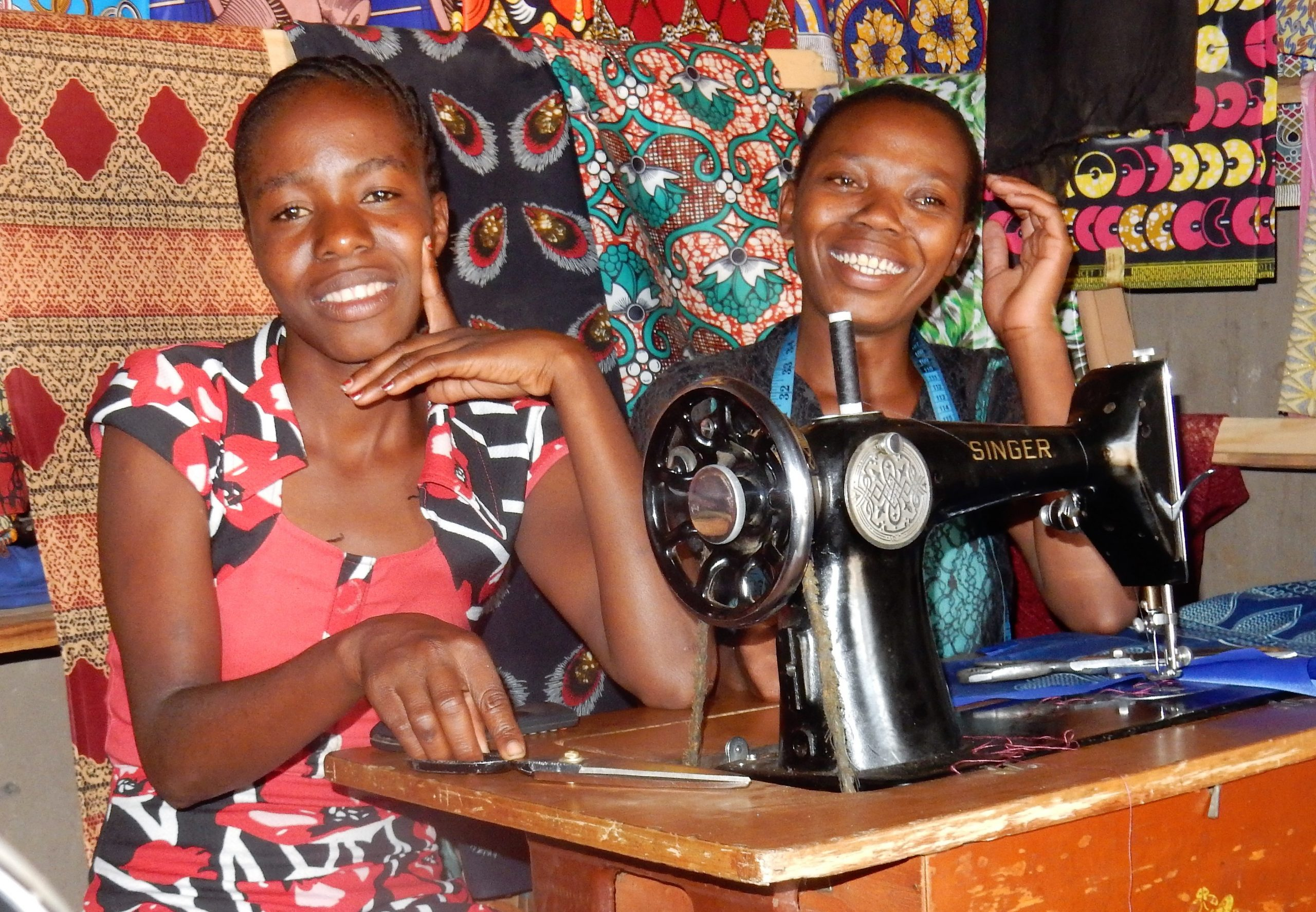 Two female tailors sit smiling behind a sewing machine