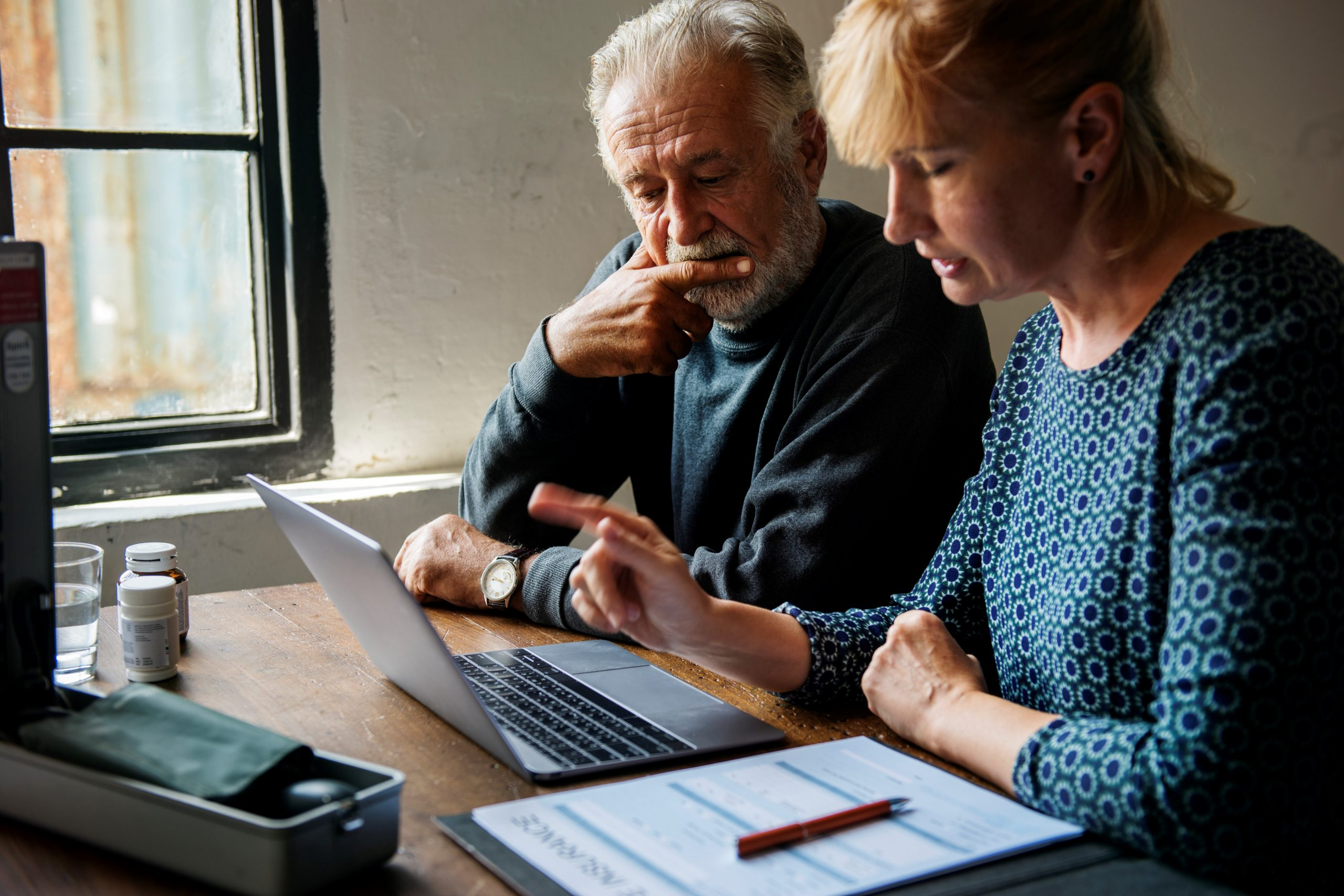Man and woman look thoughtfully at a laptop screen