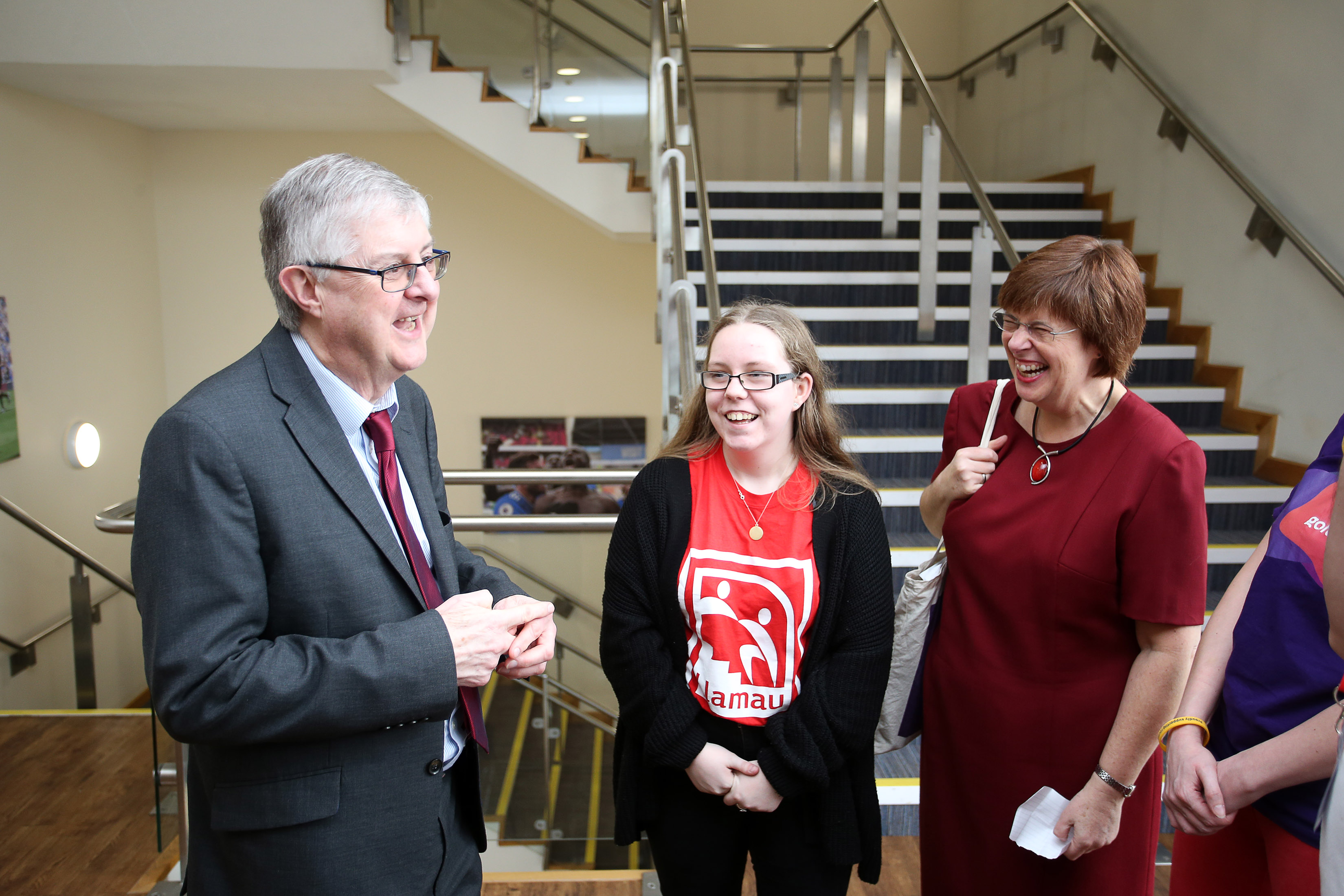 First Minister Mark Drakeford, WCVA Chief Executive Ruth Marks and a young woman stand smiling in front of some stairs