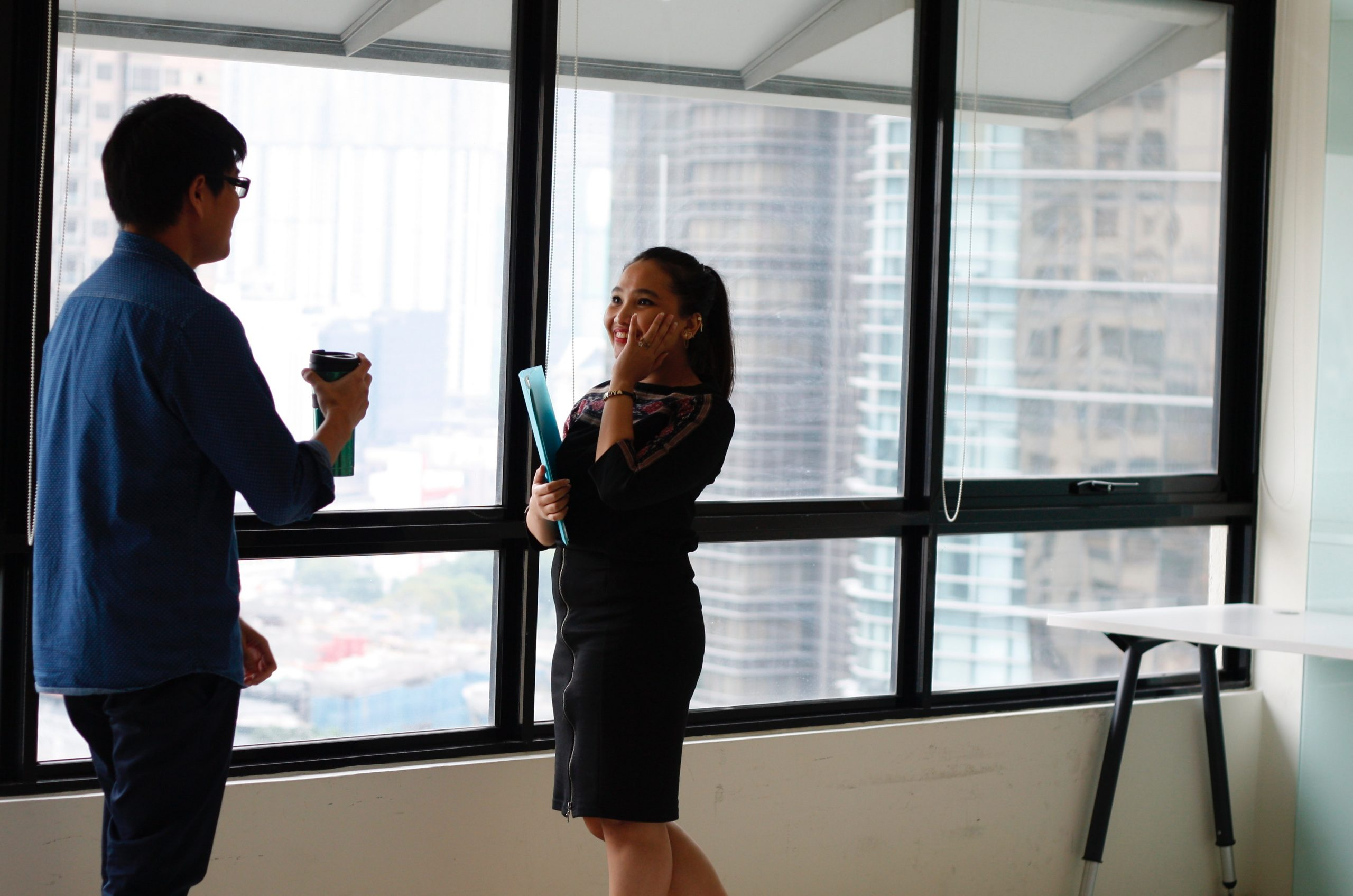 A man and a woman laugh as they talk to each other near the windows in an office