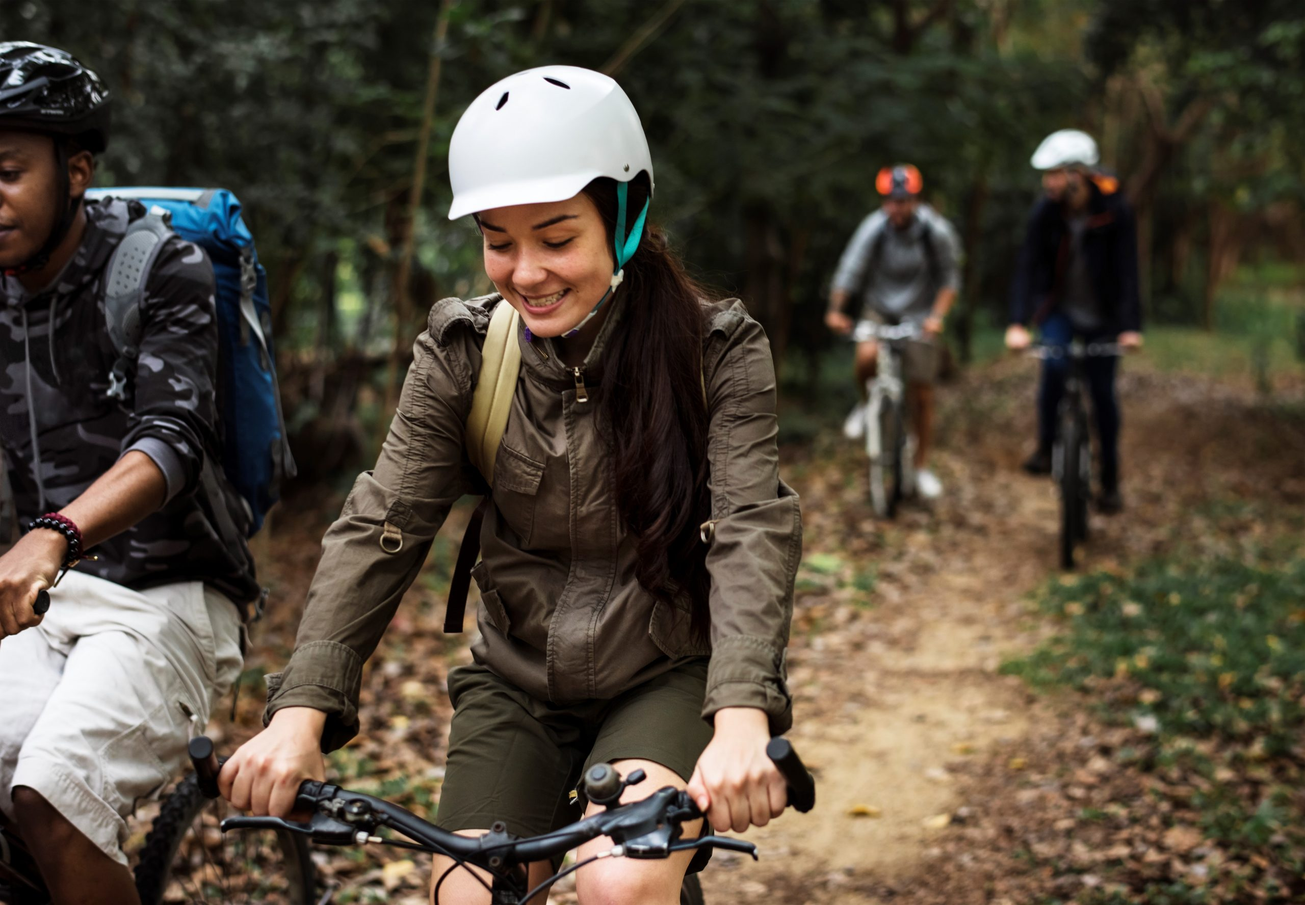 People ride their bikes, smiling, through some woodland