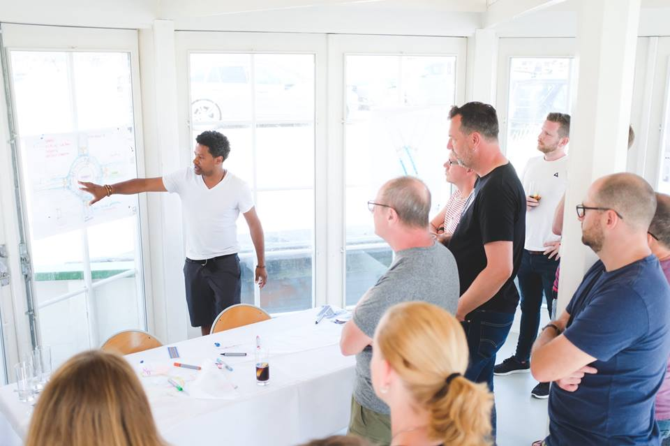 A group of people stand in a white room with wall-height windows and glass doors as a man points to blueprints taped to them
