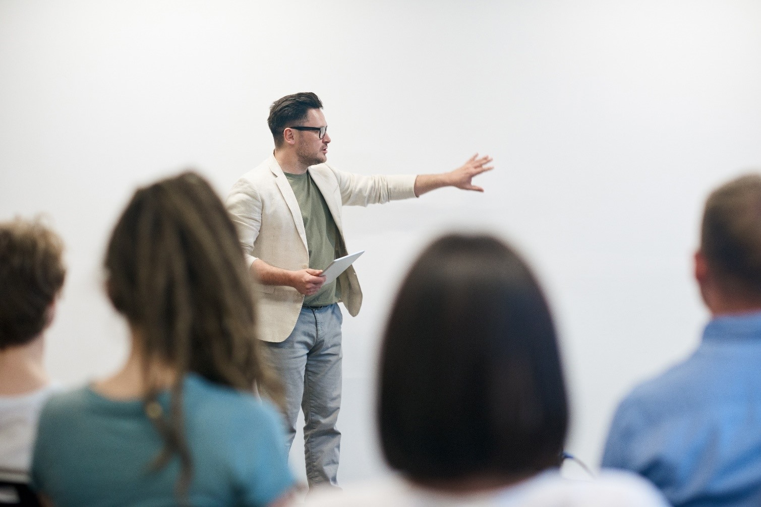 A man standing in front of an audience presenting enthusiastically