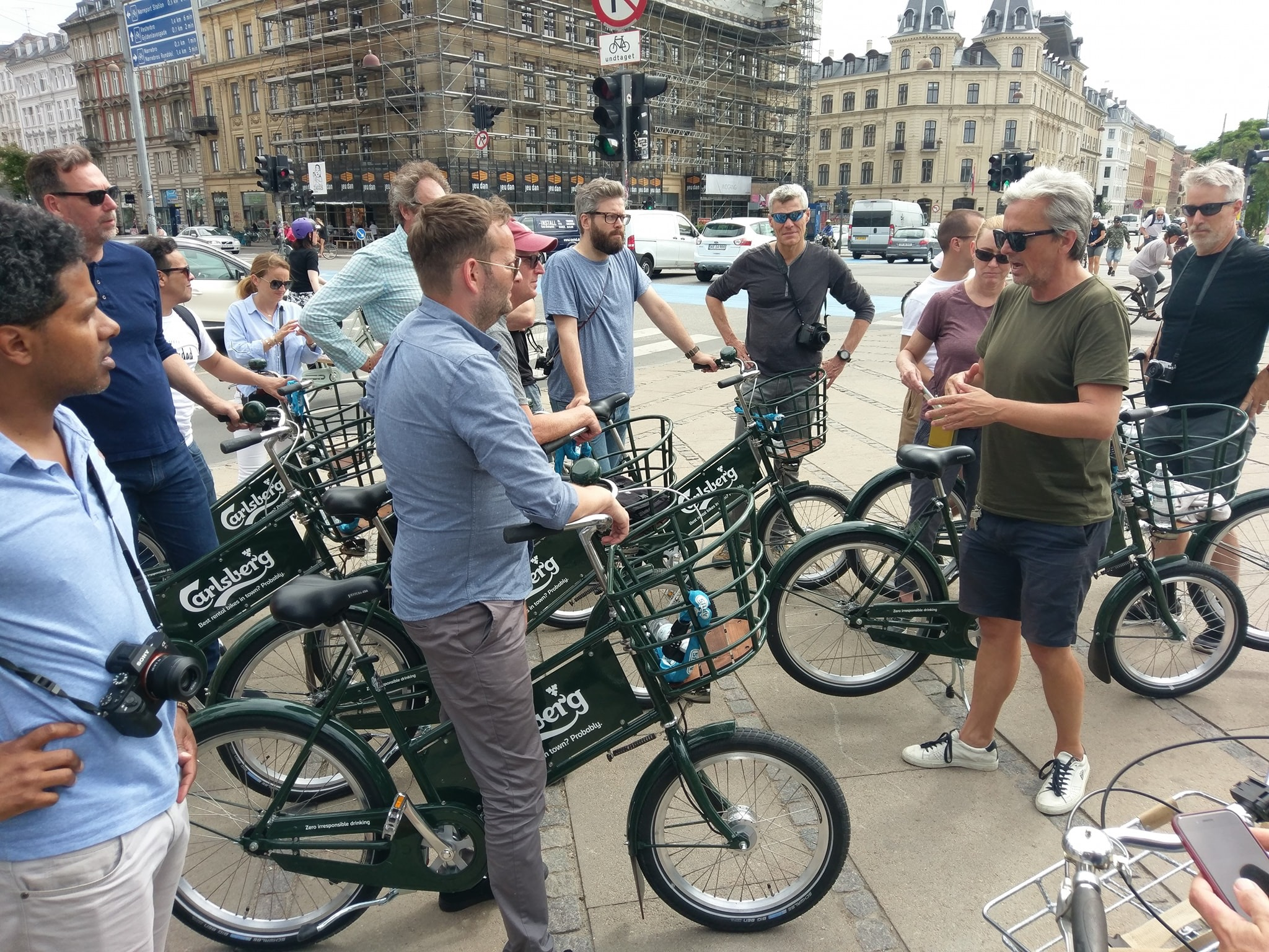 People on bikes in city listening to someone speak
