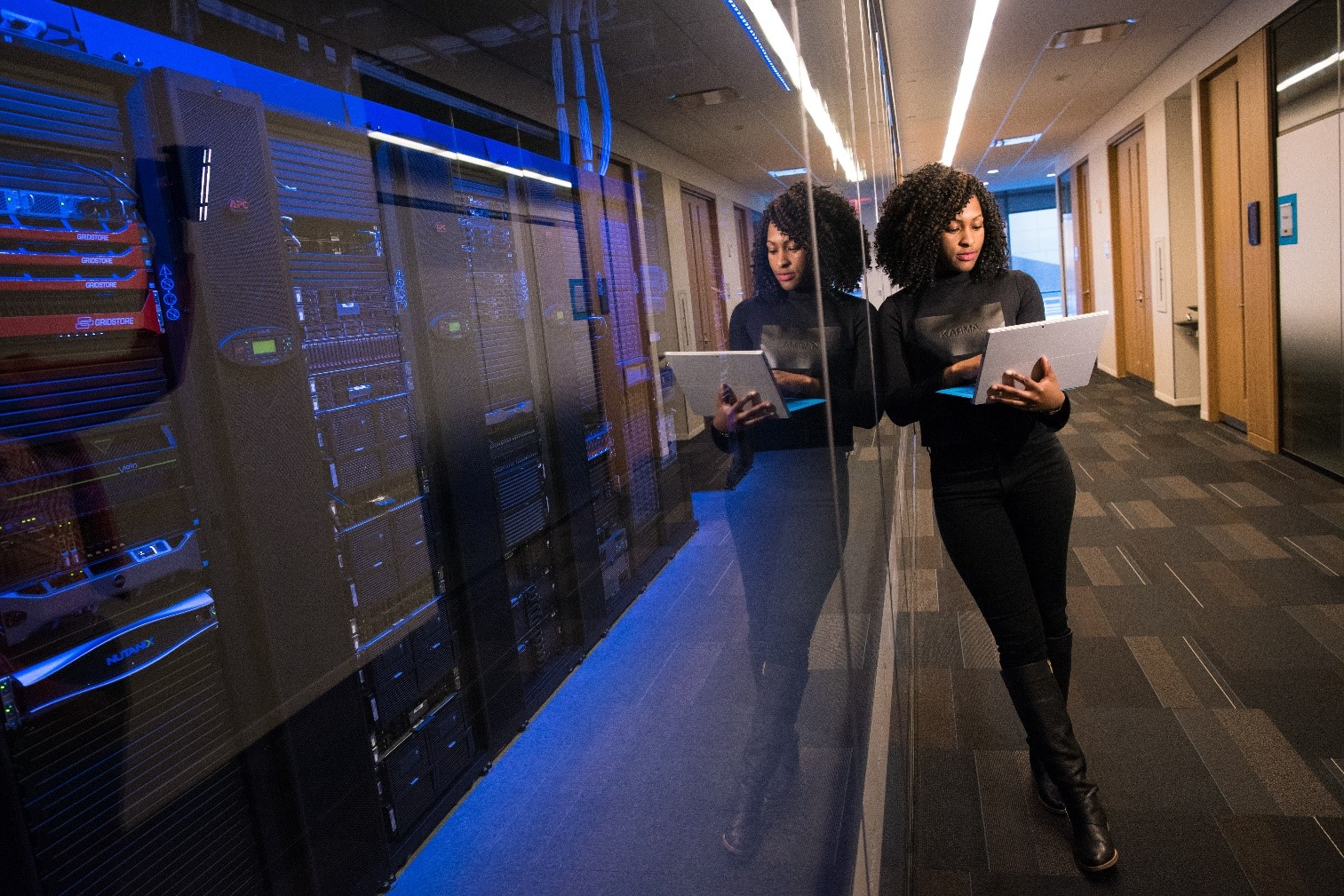 Woman on laptop standing in front of server wall