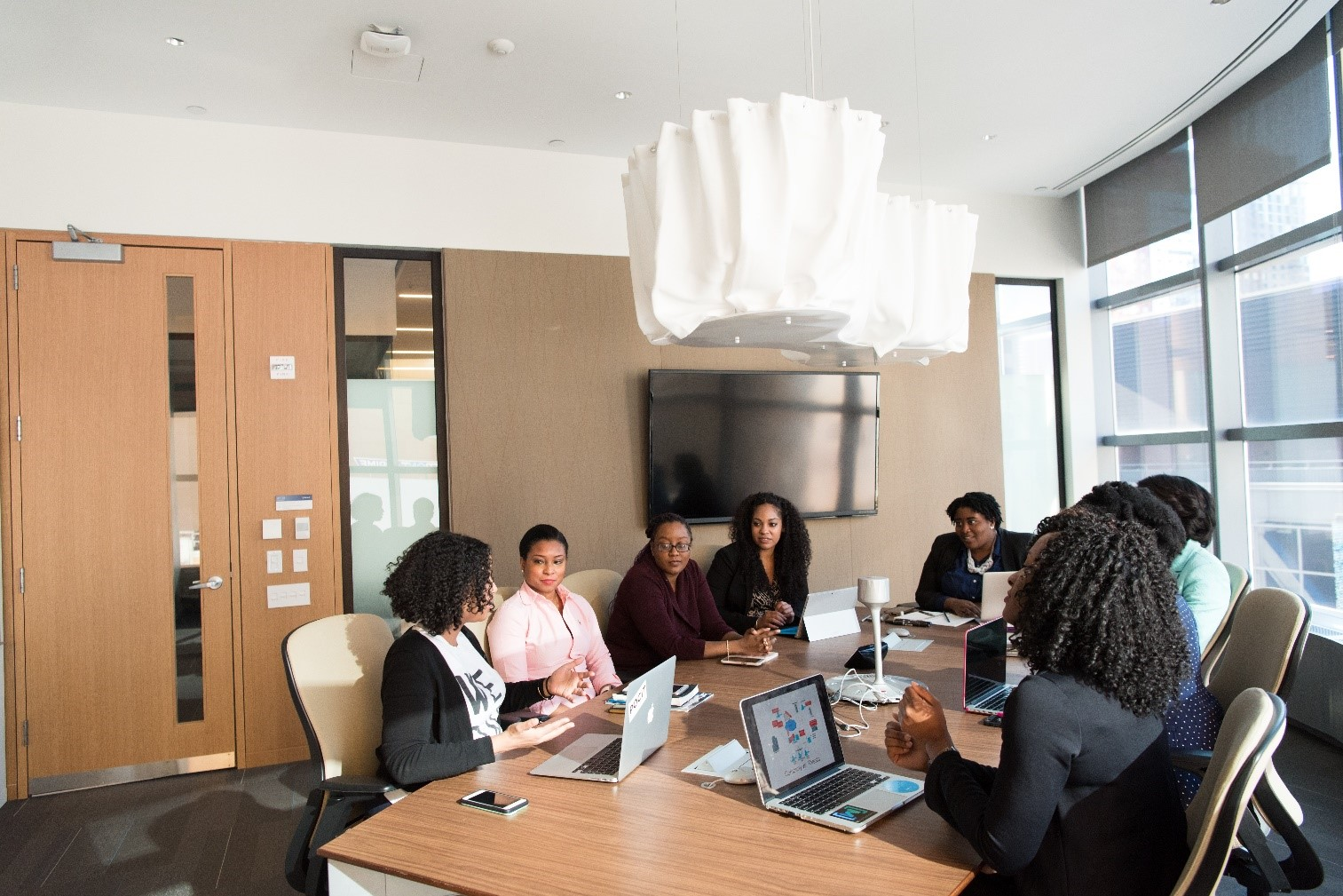 Women in a meeting sit at a table in a boardroom