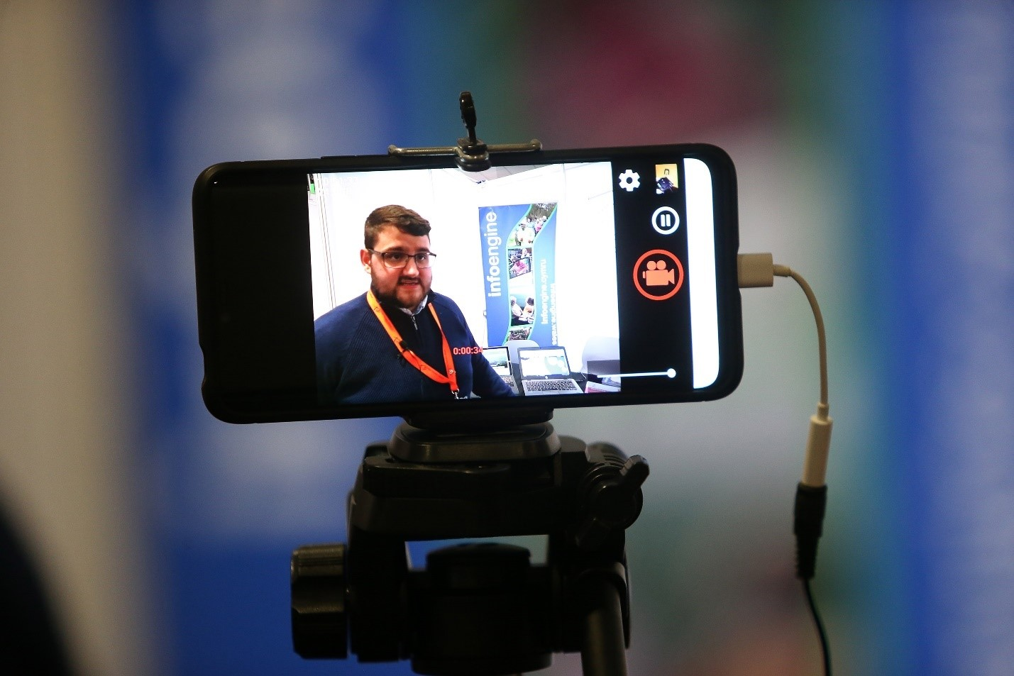 Picture of a man in front of an event stand as viewed on a phone screen