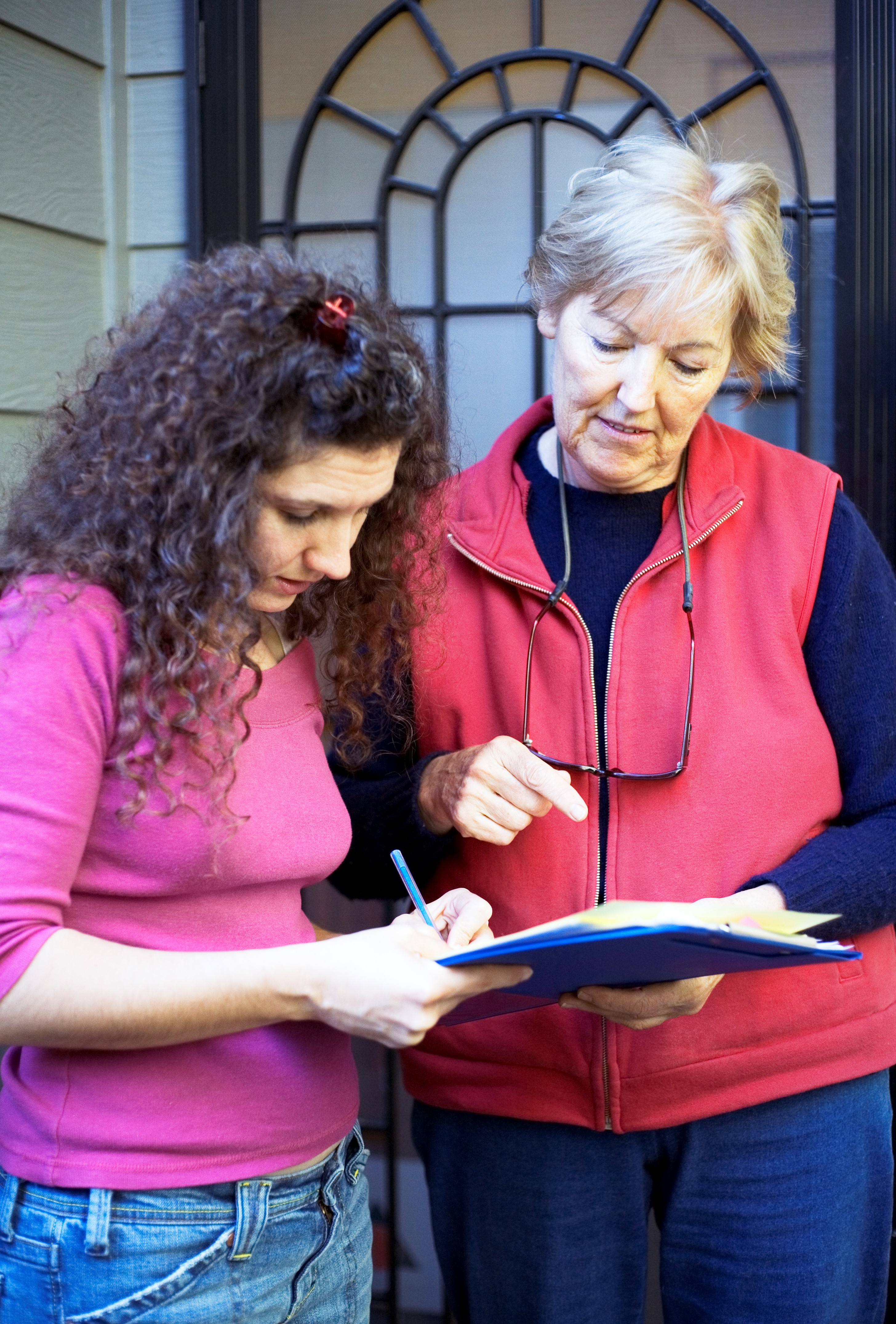 One woman holds a clipboard while another woman signs something on it