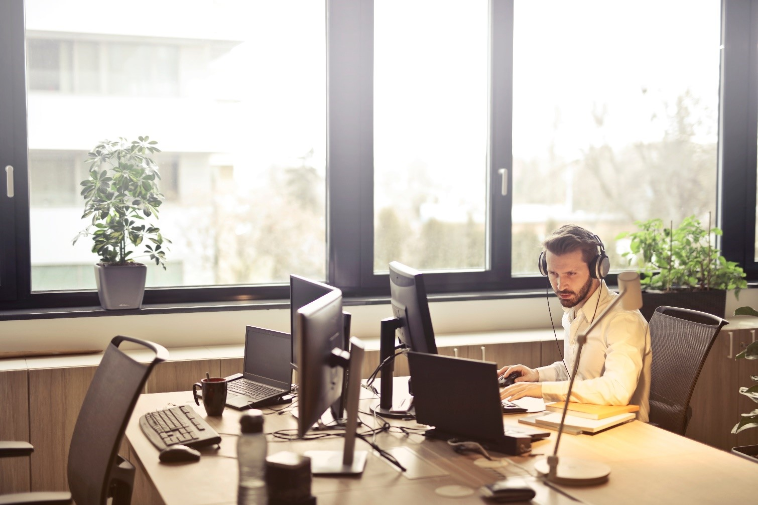 A man with headphones on at a desktop computer next to a window