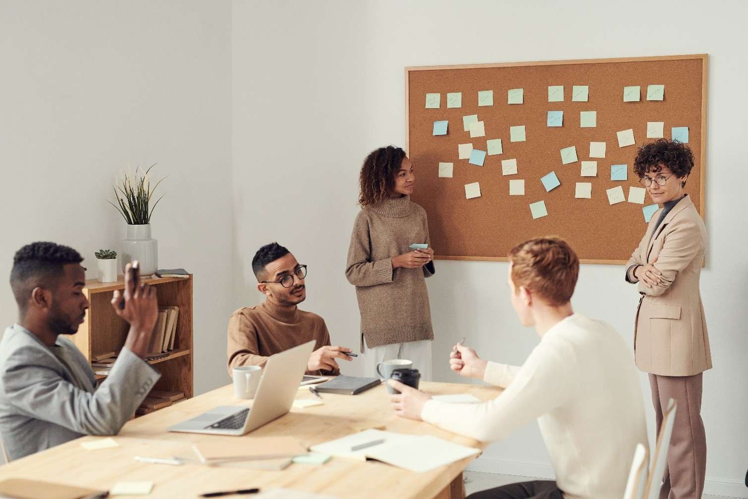 Group of people planning in meeting room around cork board