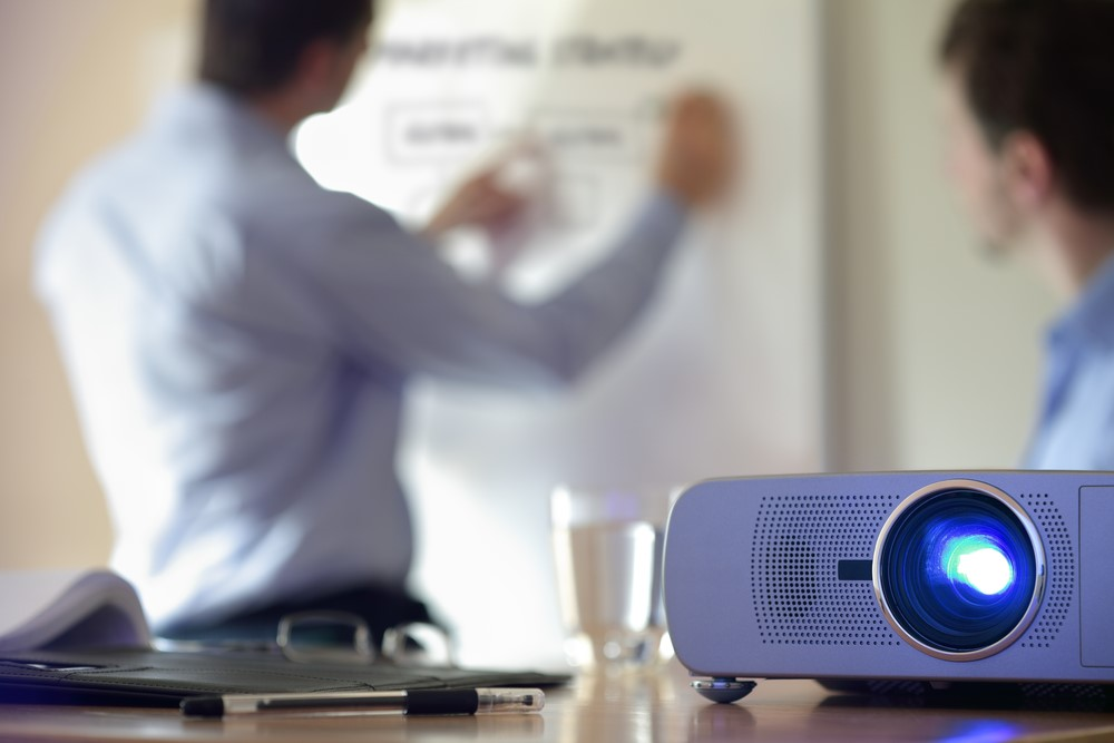 Projector with people in background writing on whiteboard