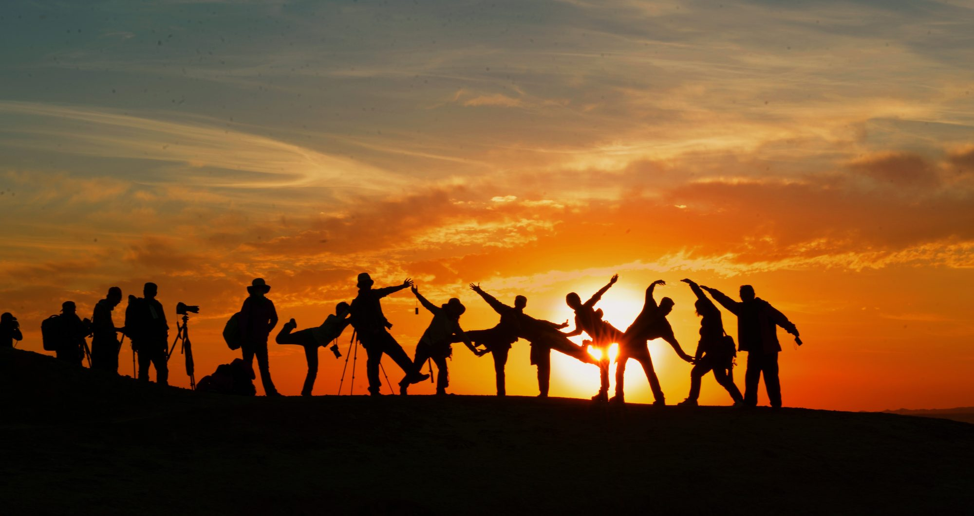 A group of people stand in front of the horizon, the light showing only their silhouettes as they make shapes