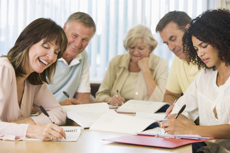 A group of people sit around a table smiling and taking notes