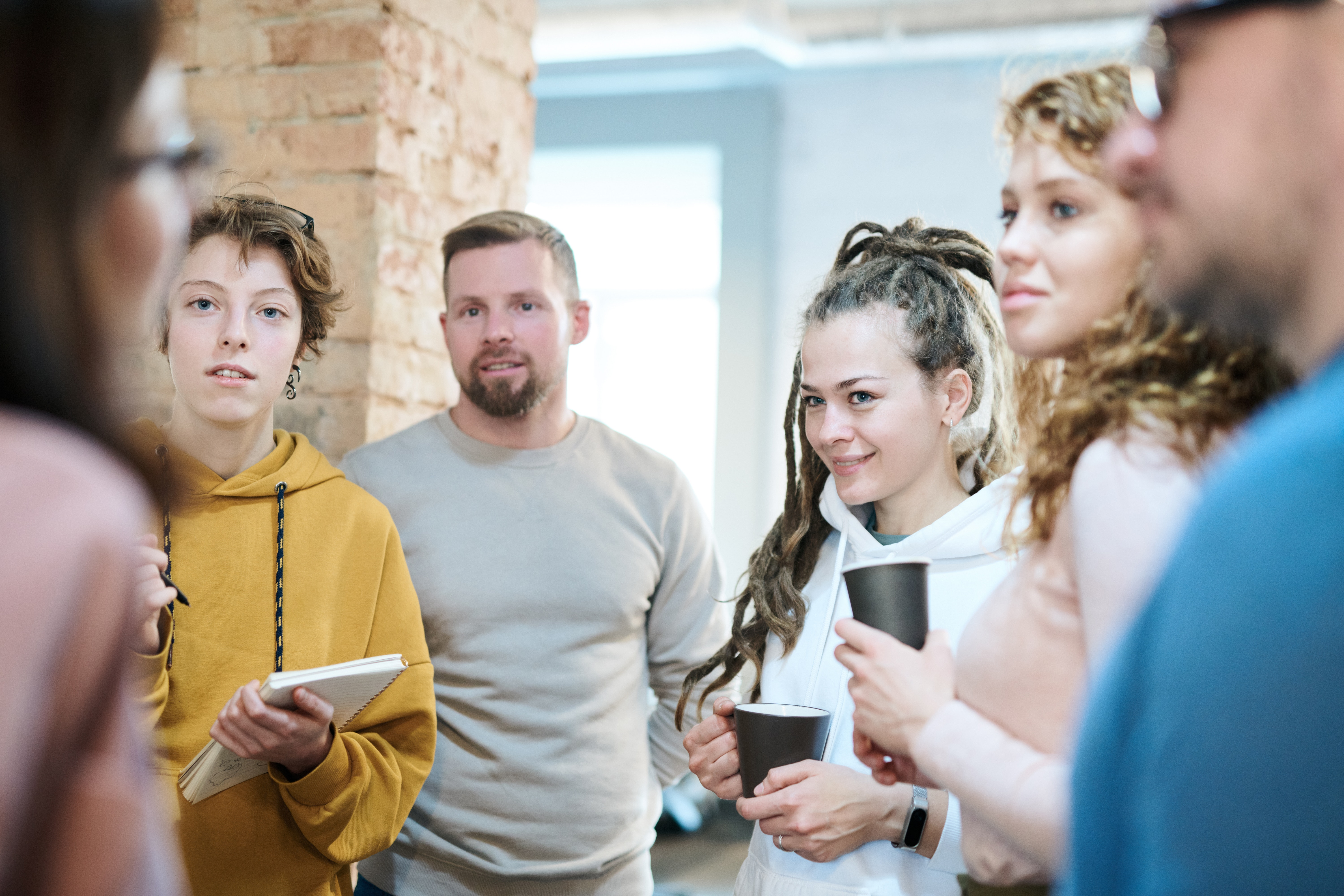 five people listening intently to someone speak in office