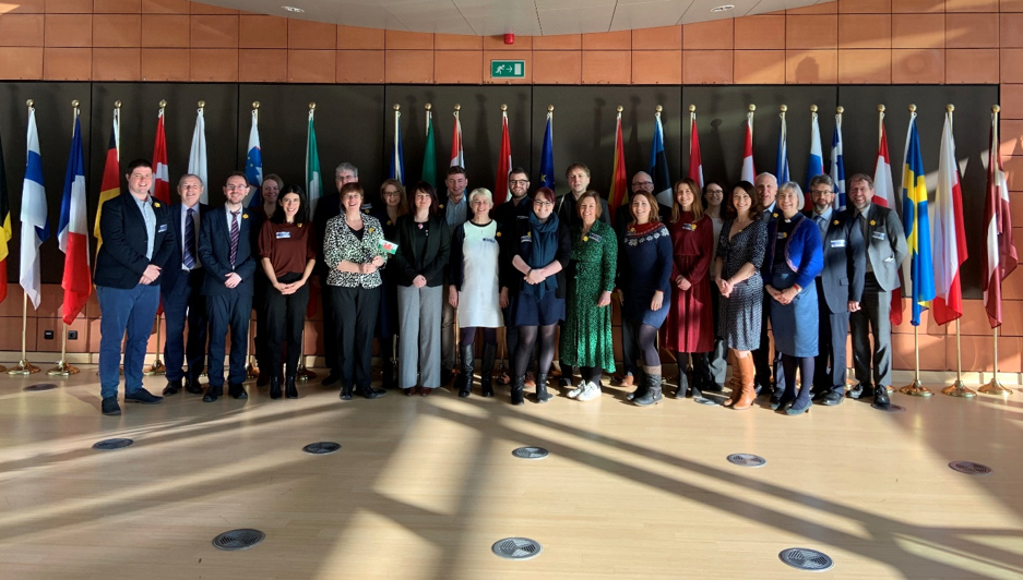 Welsh civil society delegates stand smiling in a hallway at an EU parliament building, backed by European flags