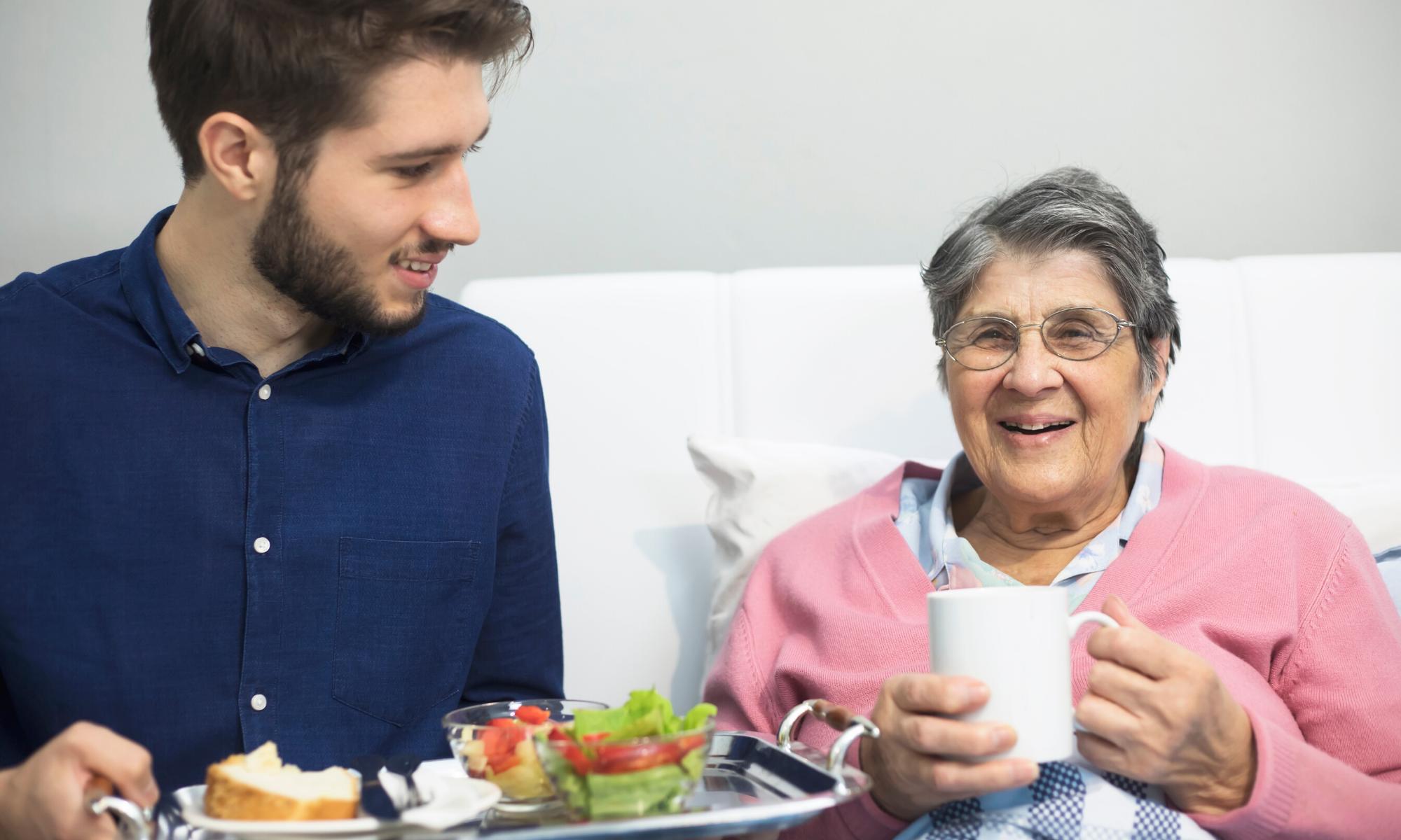 volunteer brings food to smiling older woman in bed