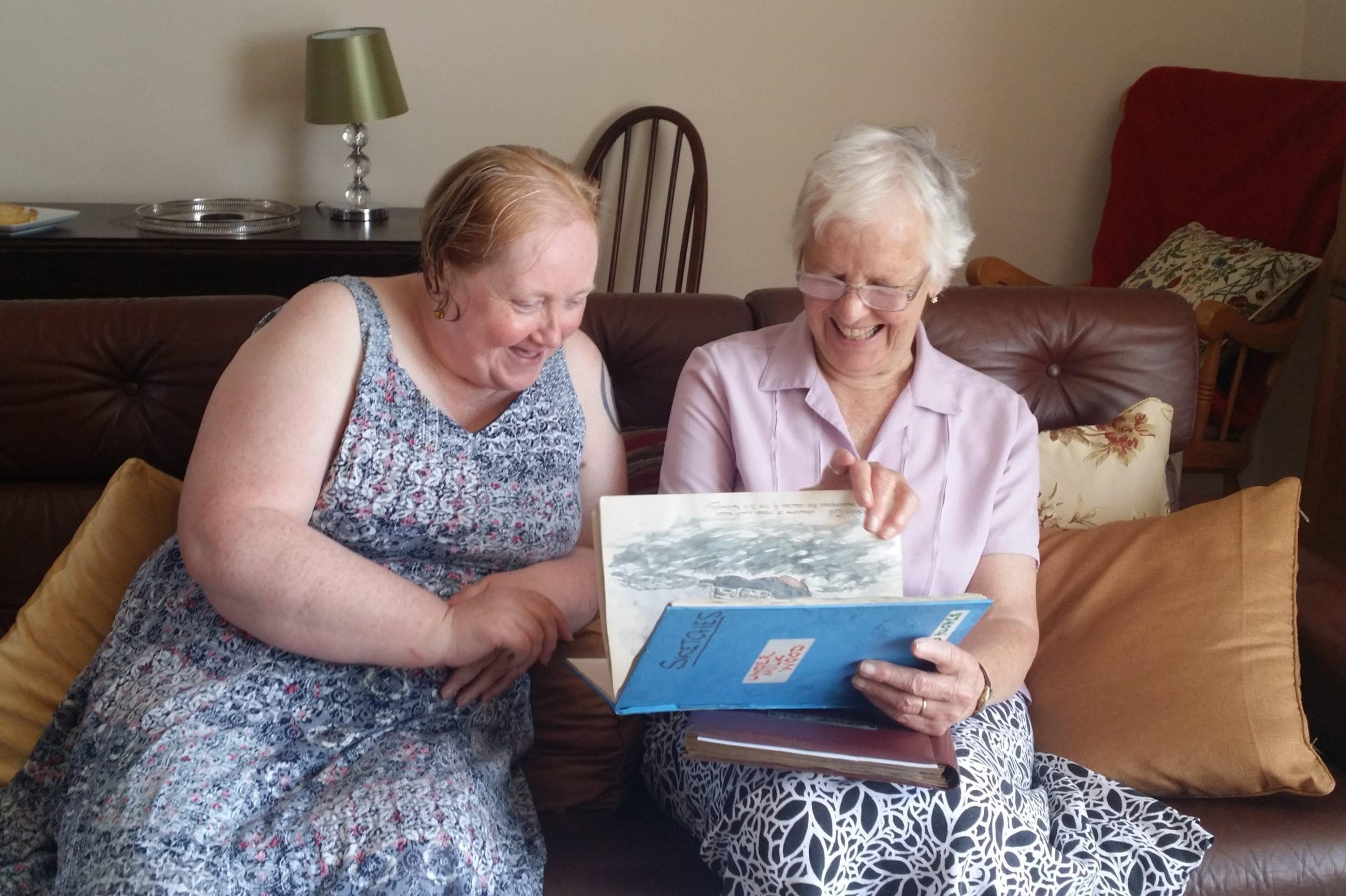 Two women sitting on a sofa look through an old sketchbook