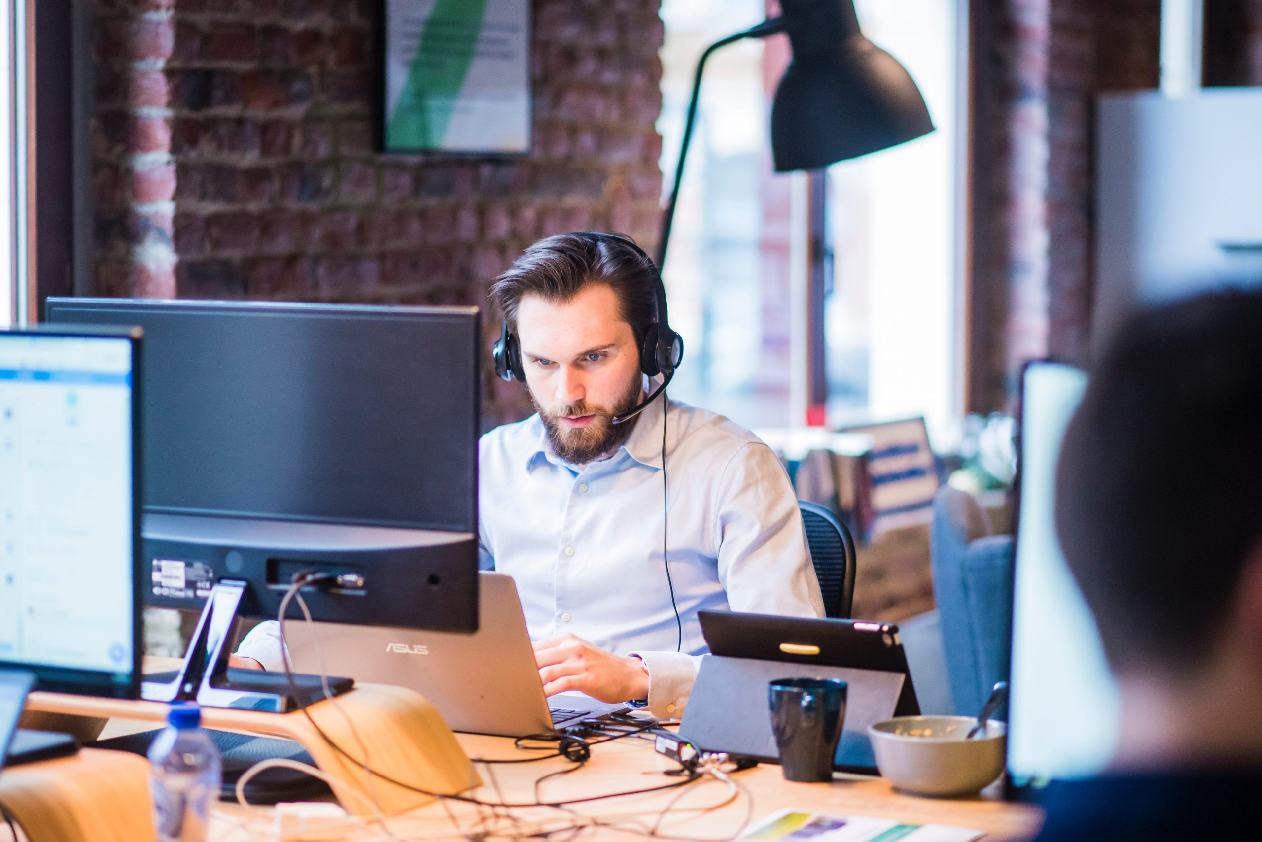 man in shirt looking at laptop