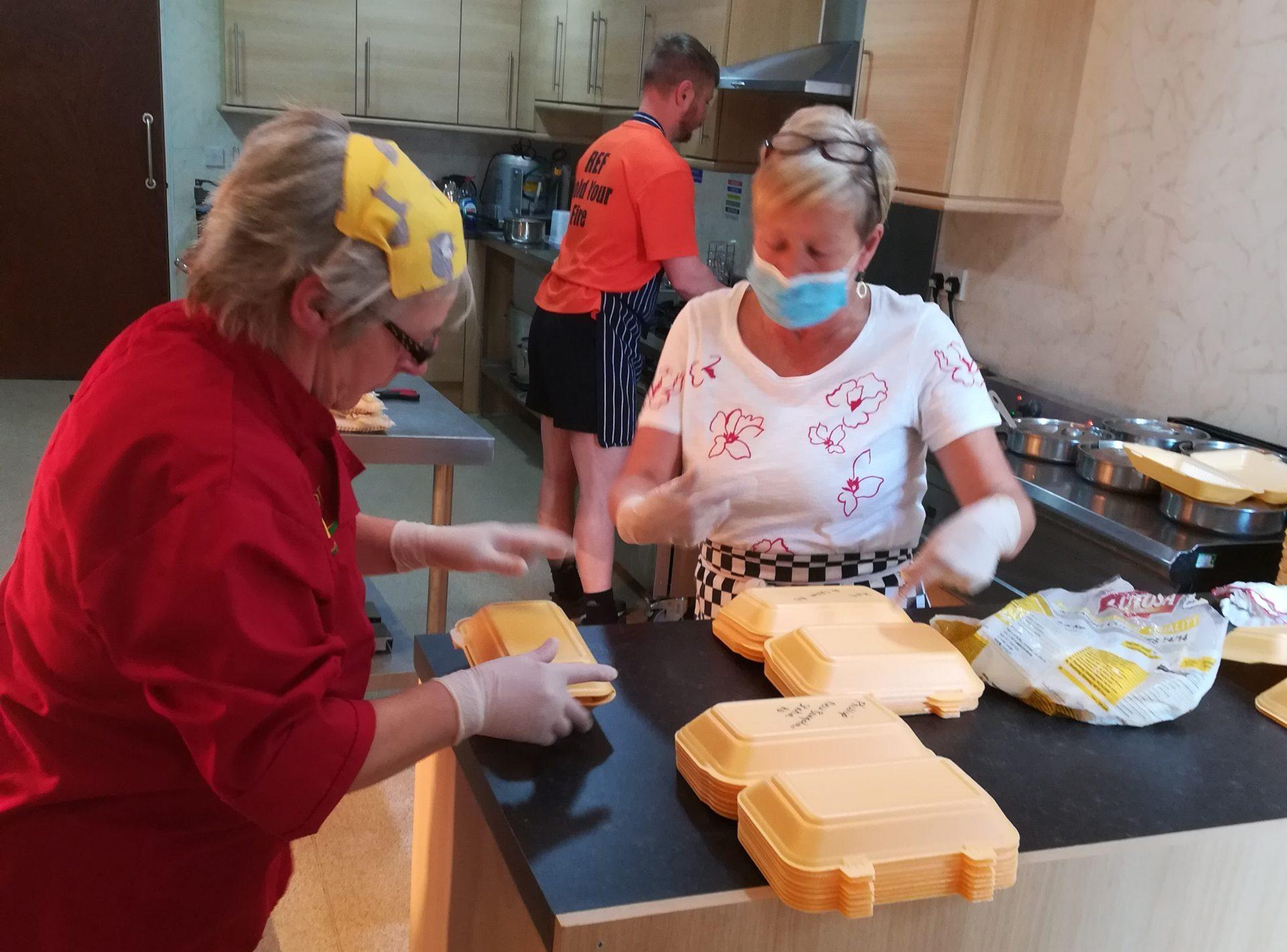 volunteers help fill food packs during coronavirus crisis