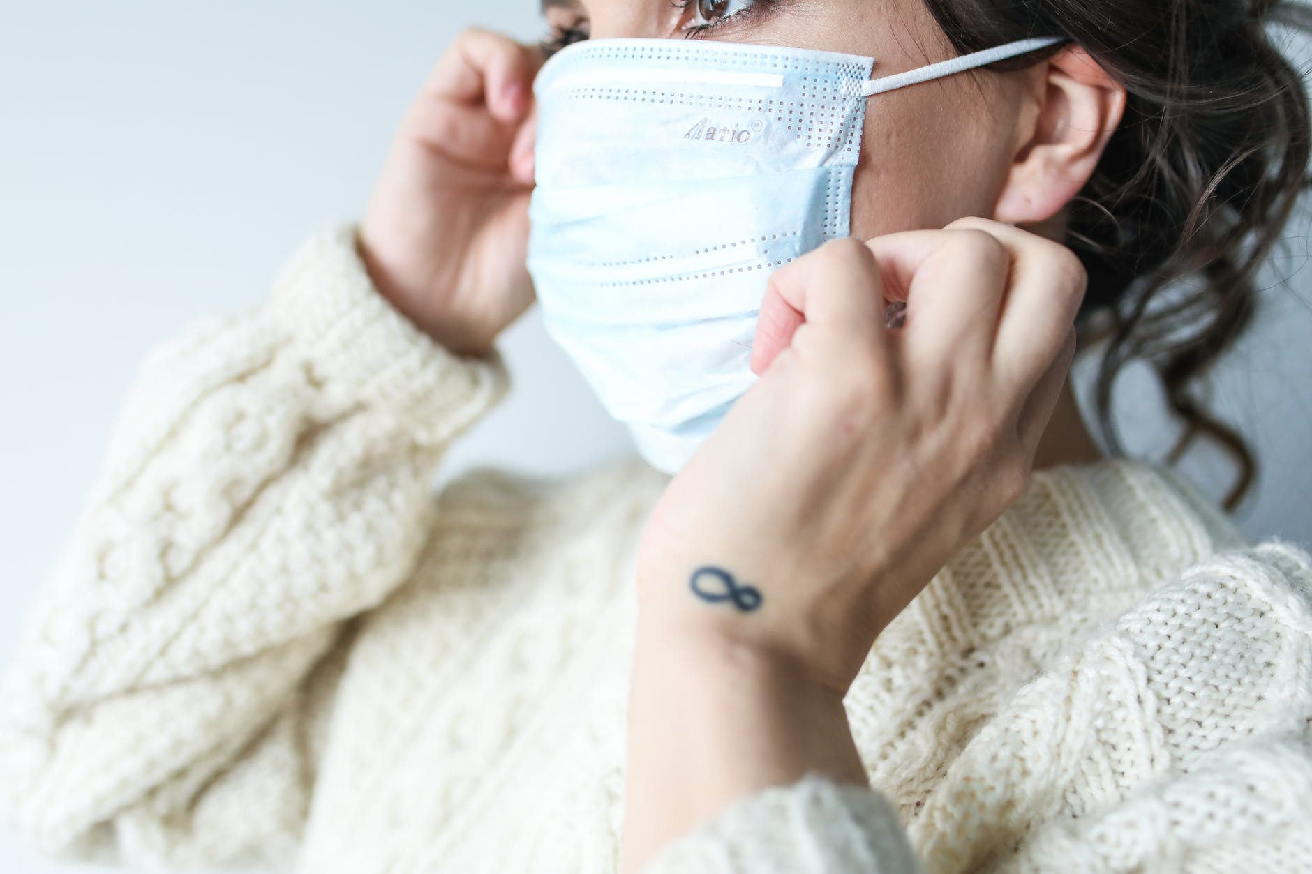 woman pulling on facemask to protect from coronavirus