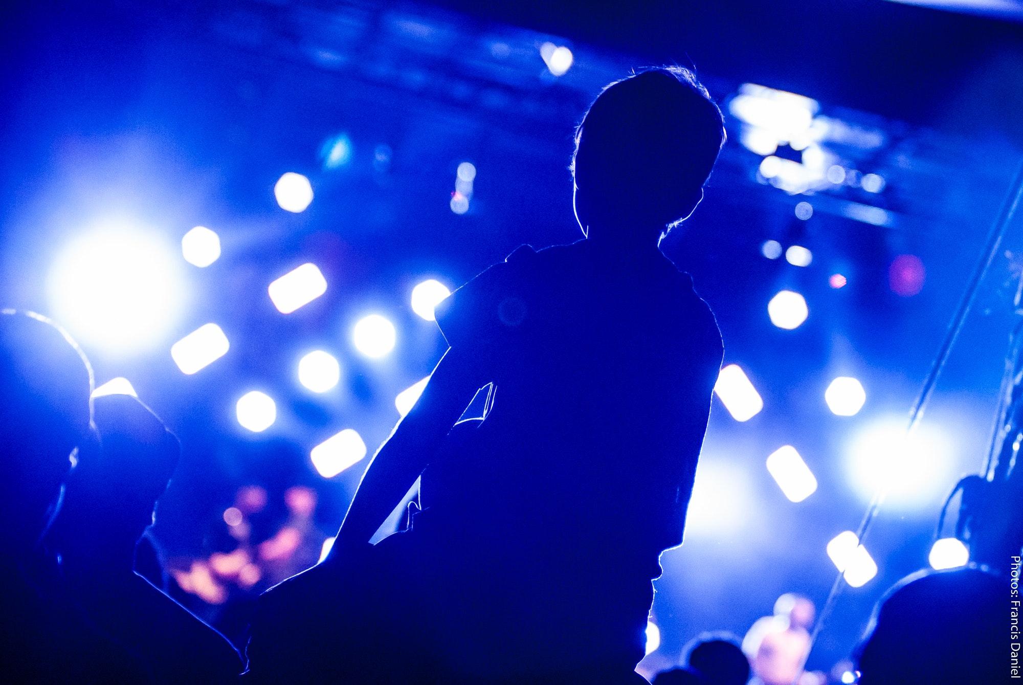 boy on shoulders watching concert in spotlight