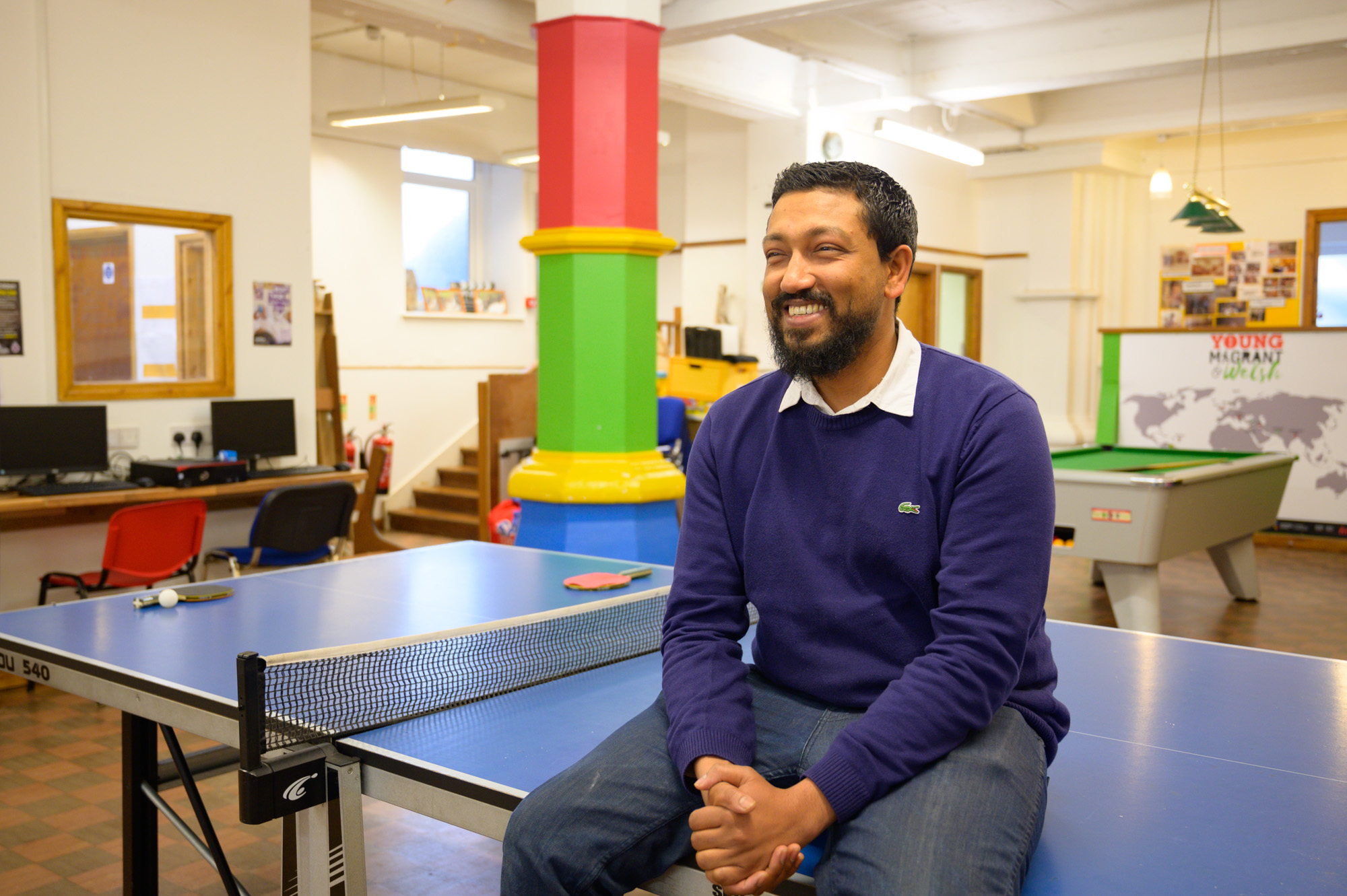 man smiling and sitting on a ping pong table at a youth centre