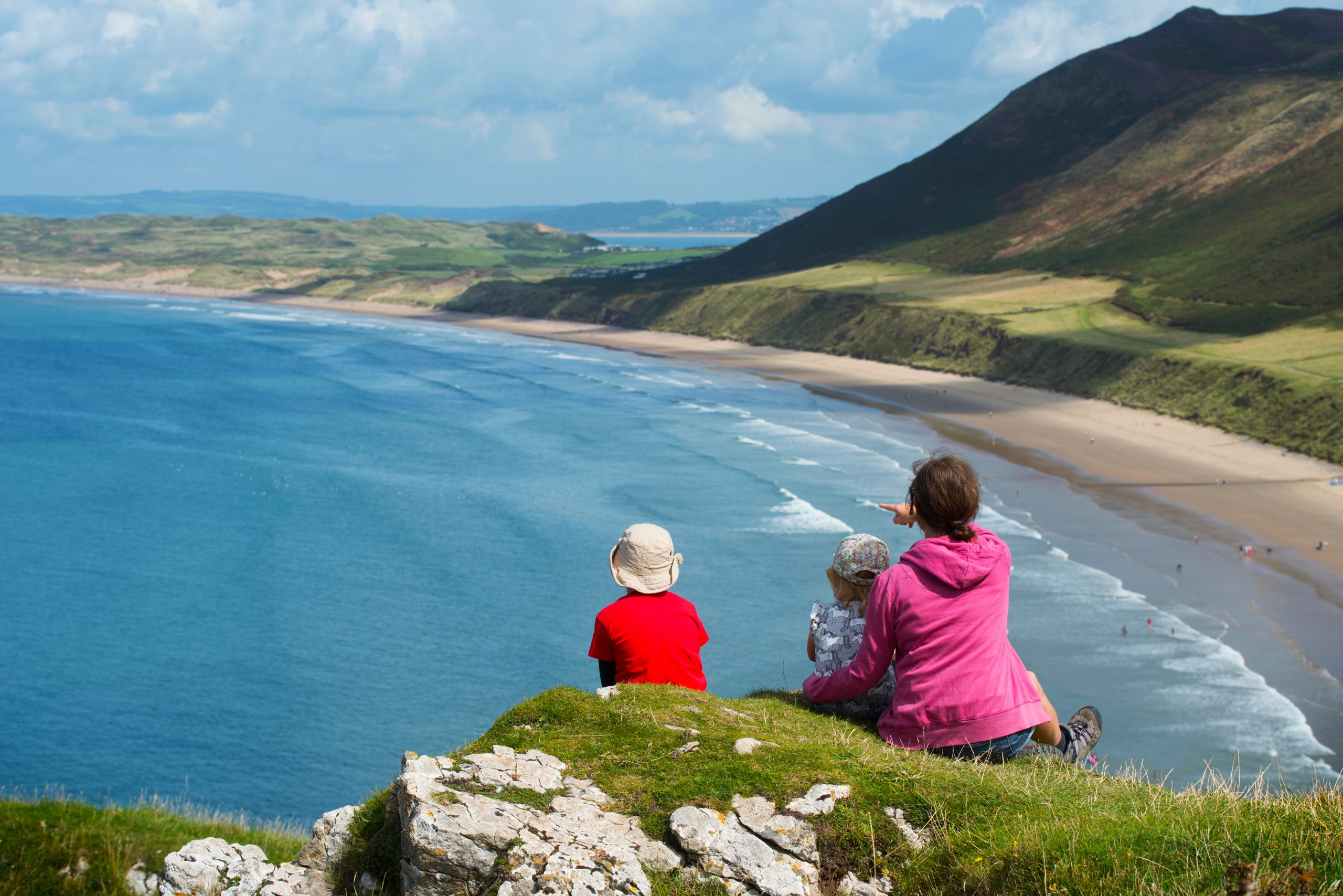 a family sit on a cliff in the sun overlooking Rhossili Bay