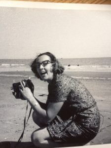 Sally's mother as a young woman taking a photo at the beach and smiling