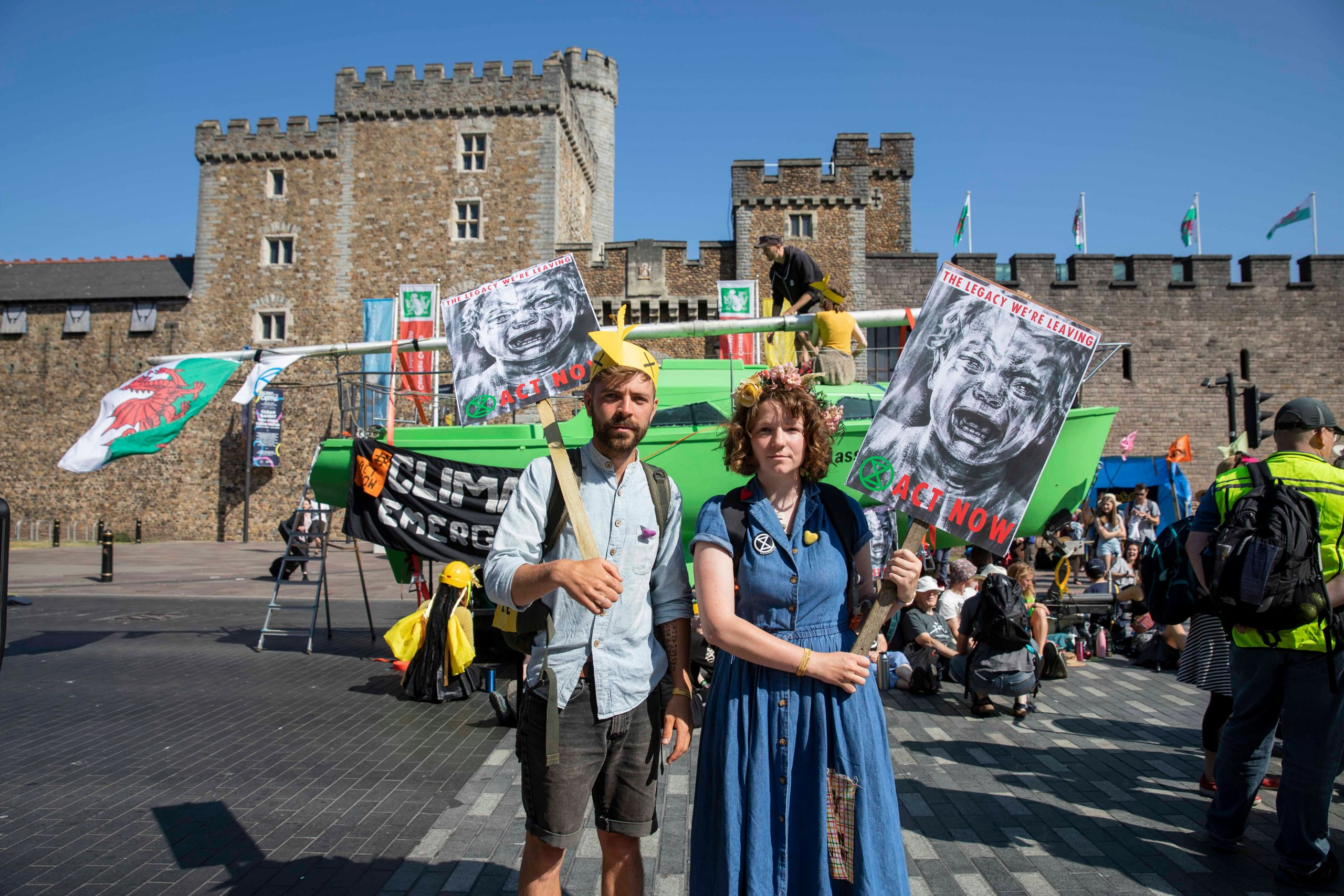 Man and woman protesting climate change in front of Cardiff Castle