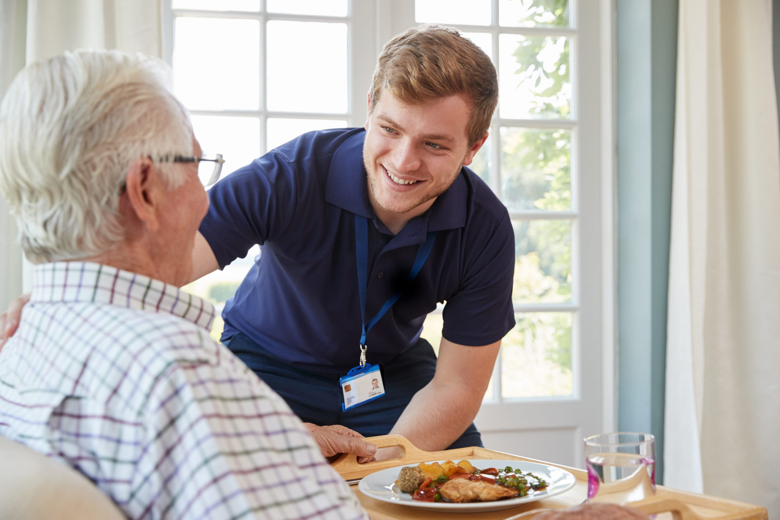 Young man helping older man with dinner