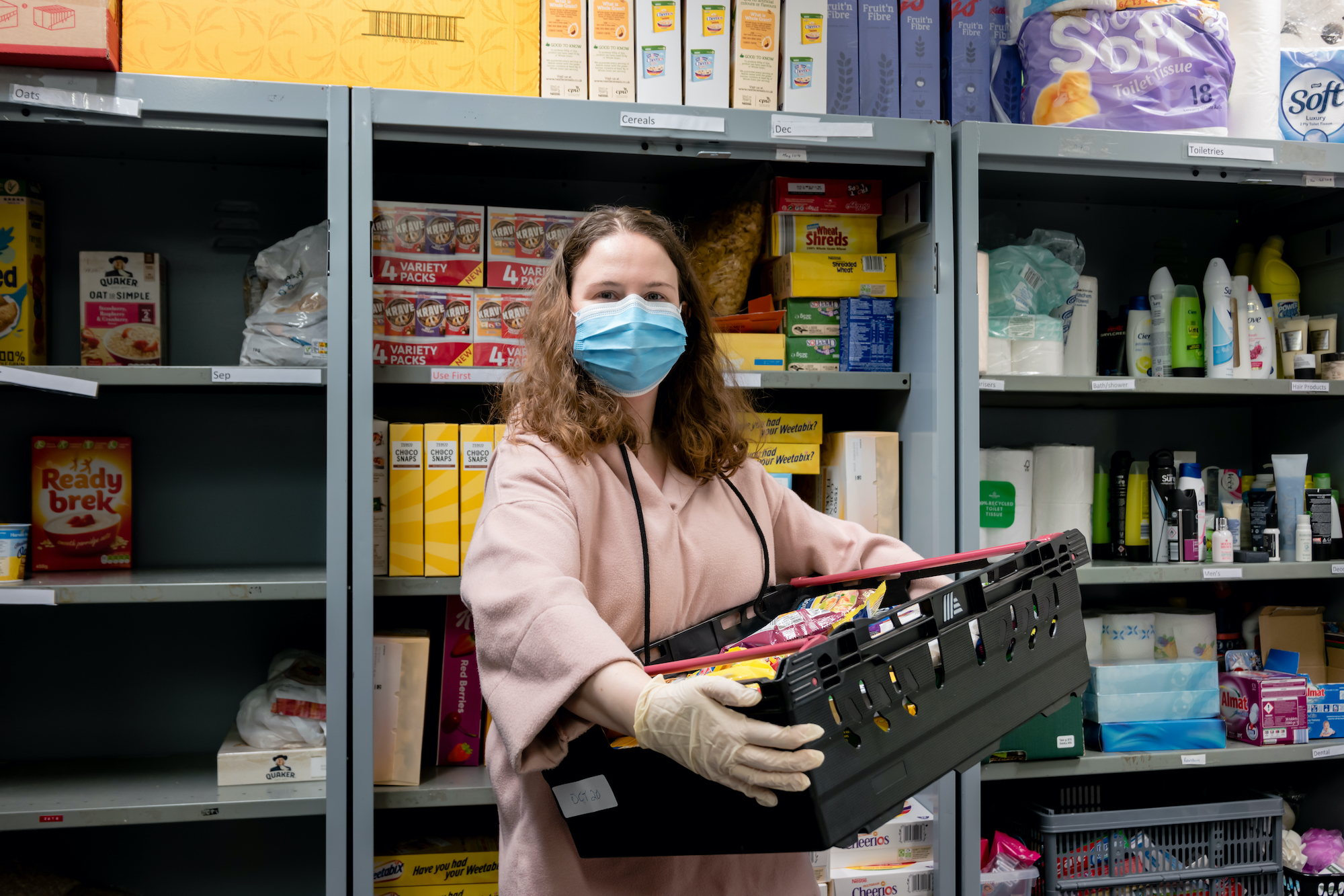 A volunteer at a food bank wears gloves and face mask PPE in the coronavirus pandemic whilst packing a client parcel