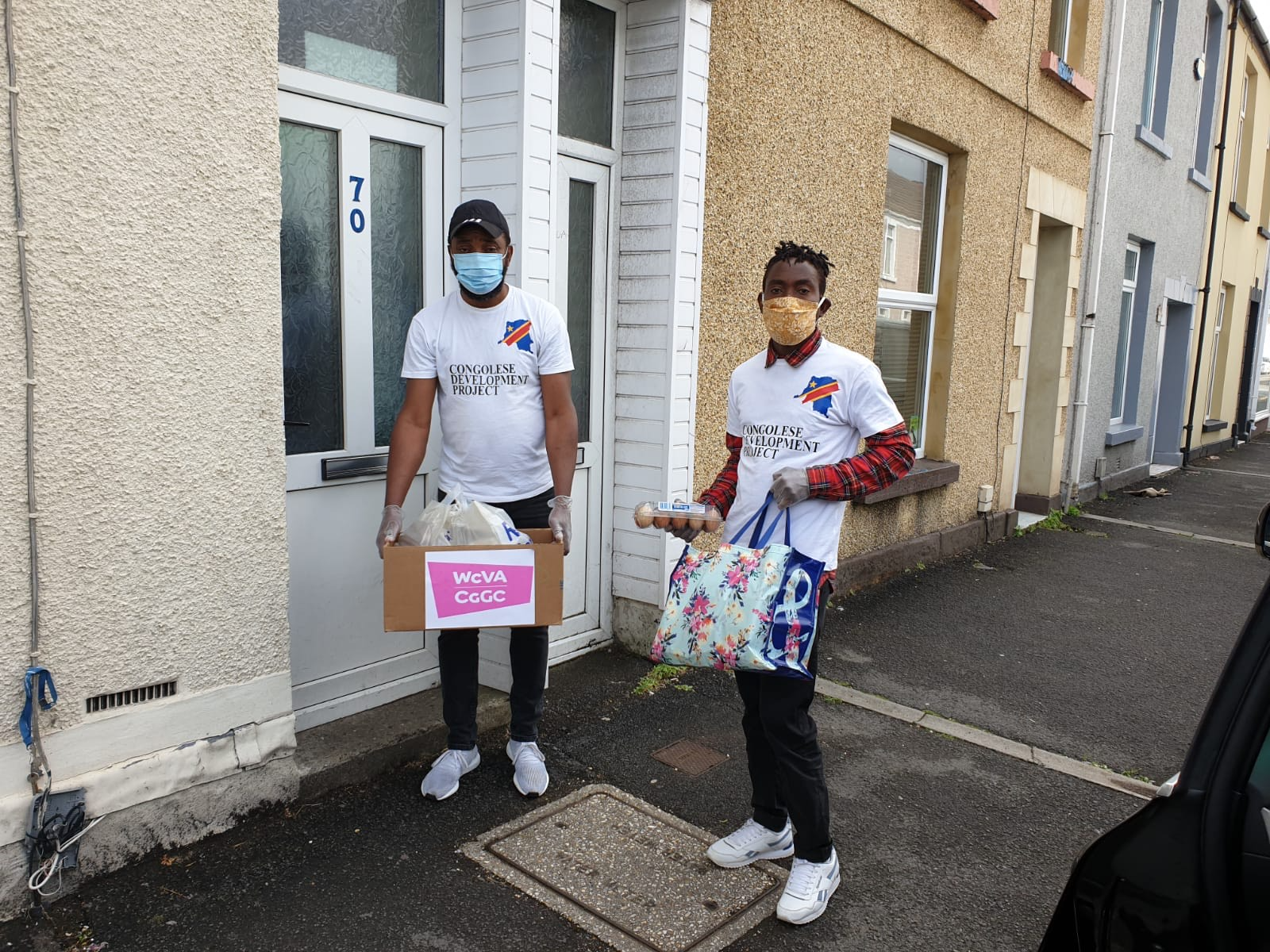 Two young black men deliver food items to a doorstep on a terraced street. They are wearing face masks and Congolese Development Project t-shirts