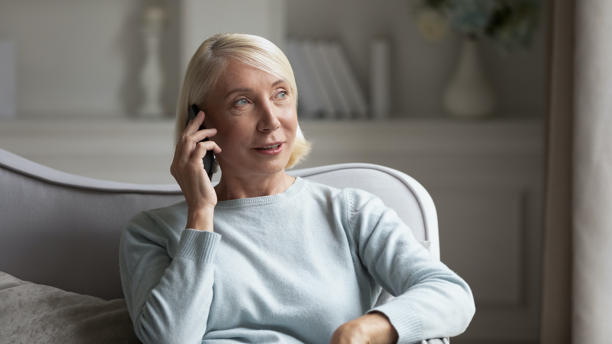 60s blonde woman sit on couch holds phone chatting with friend having pleasant distant conversation talking