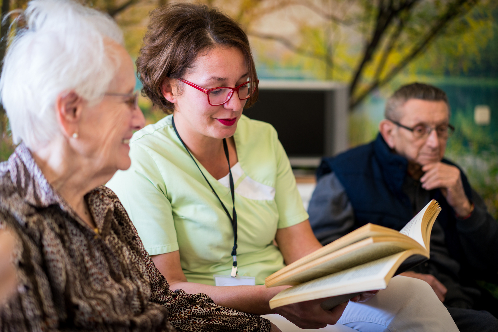 Volunteer reading a book to a group of older people