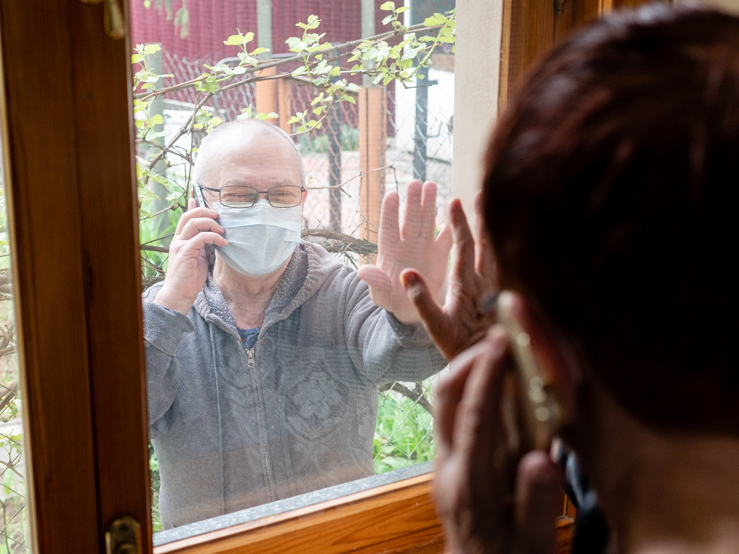 An elderly woman is talking on a cell phone with an elderly man in an antiviral mask, who is standing on the street at the window