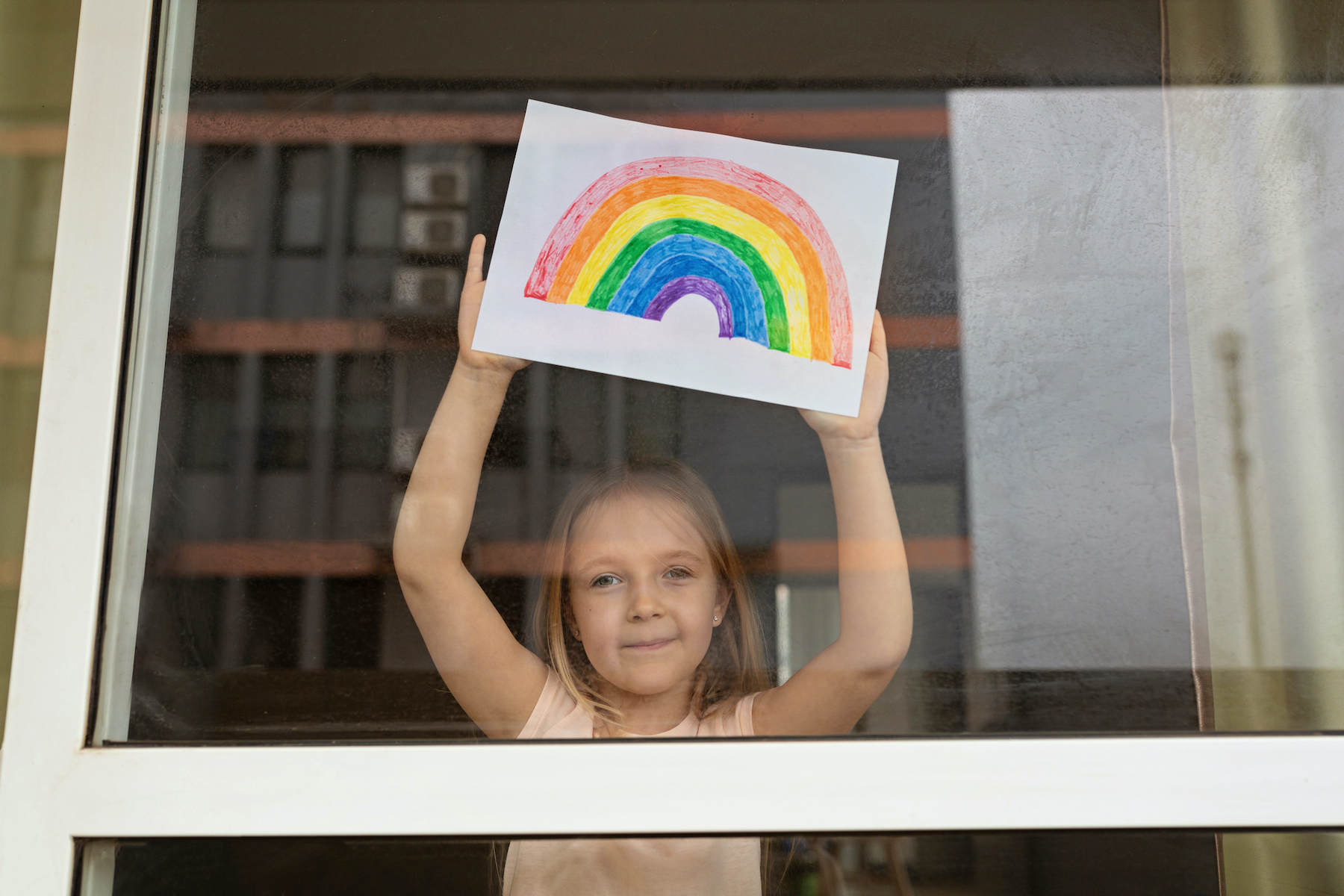 Kid painting rainbow during Covid-19 quarantine at home. Girl near window.
