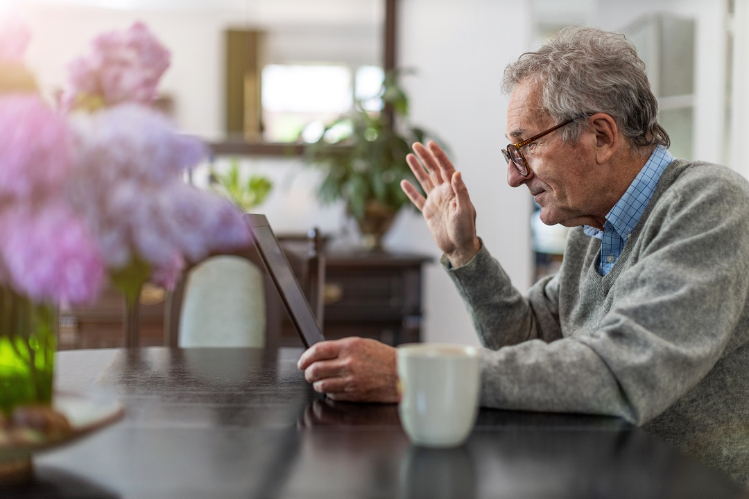 Older man on video call at home waves at his laptop
