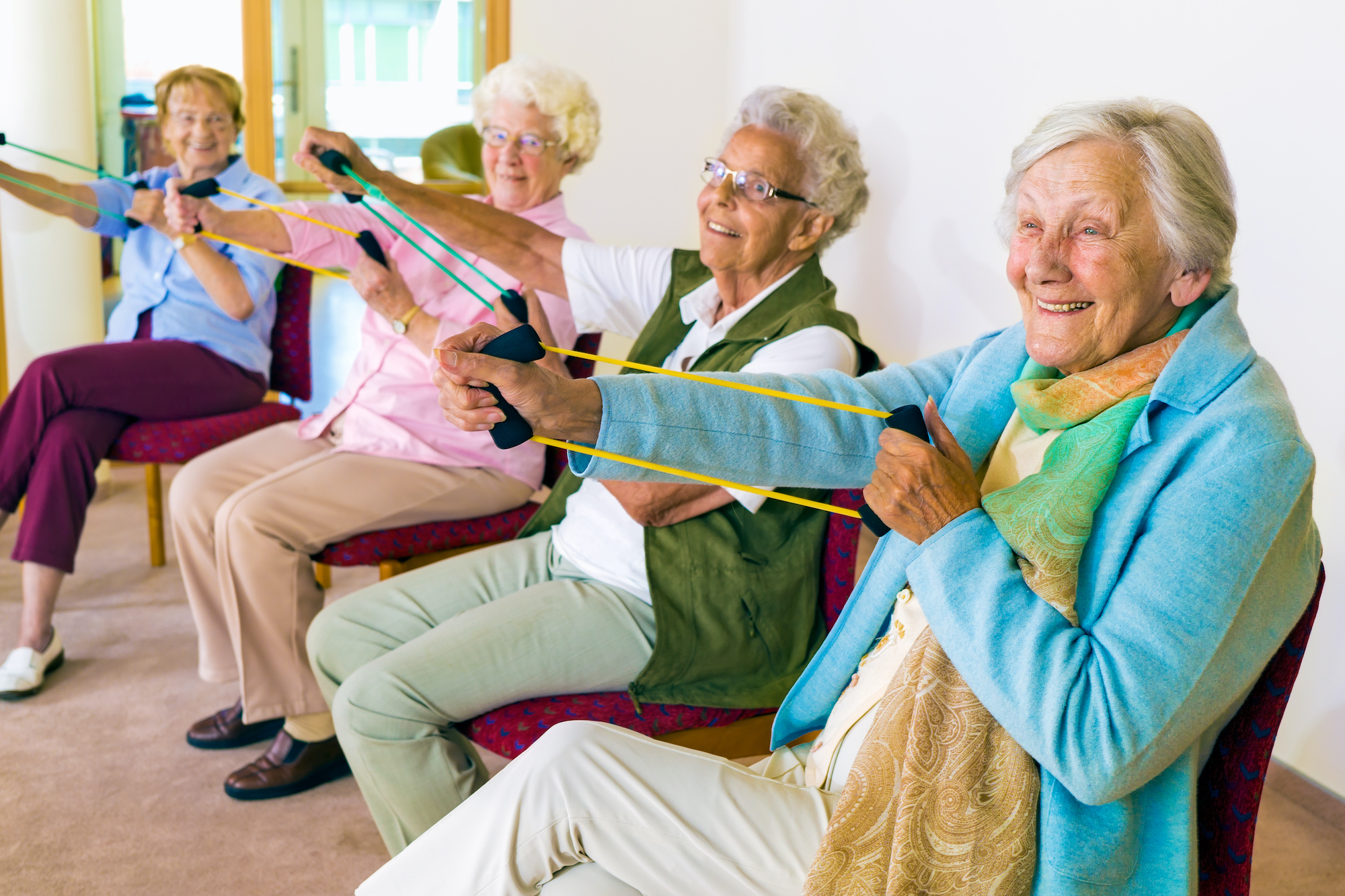 Group of four smiling senior women toning their arms with elastic strengthening bands while seated in fitness class