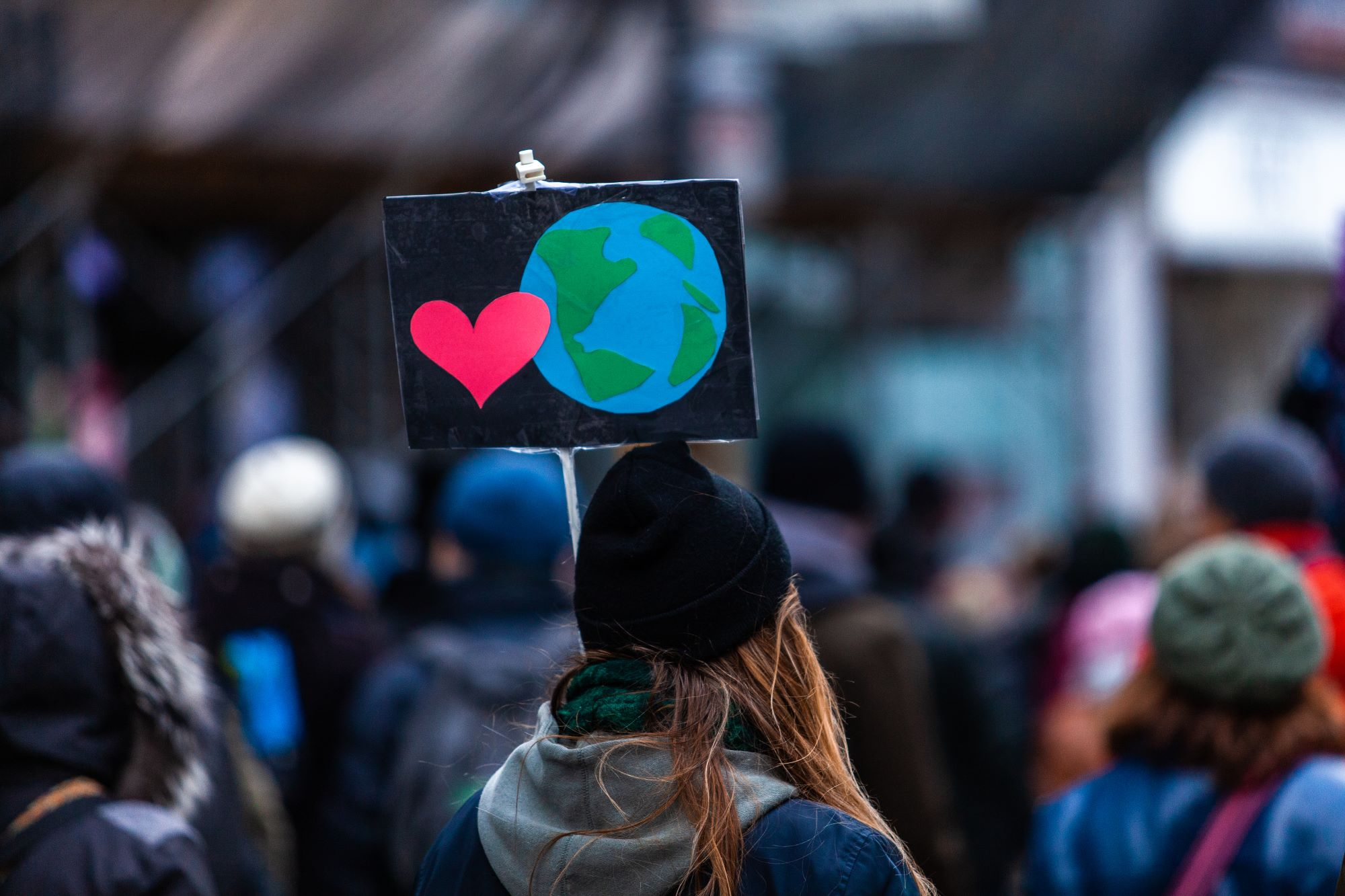 woman at protest holds sign with earth and heart on
