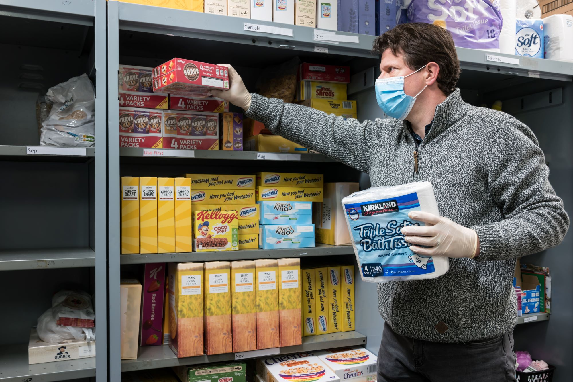 Man in mask stacks shelves at foodbank for people affected financially by coronavirus
